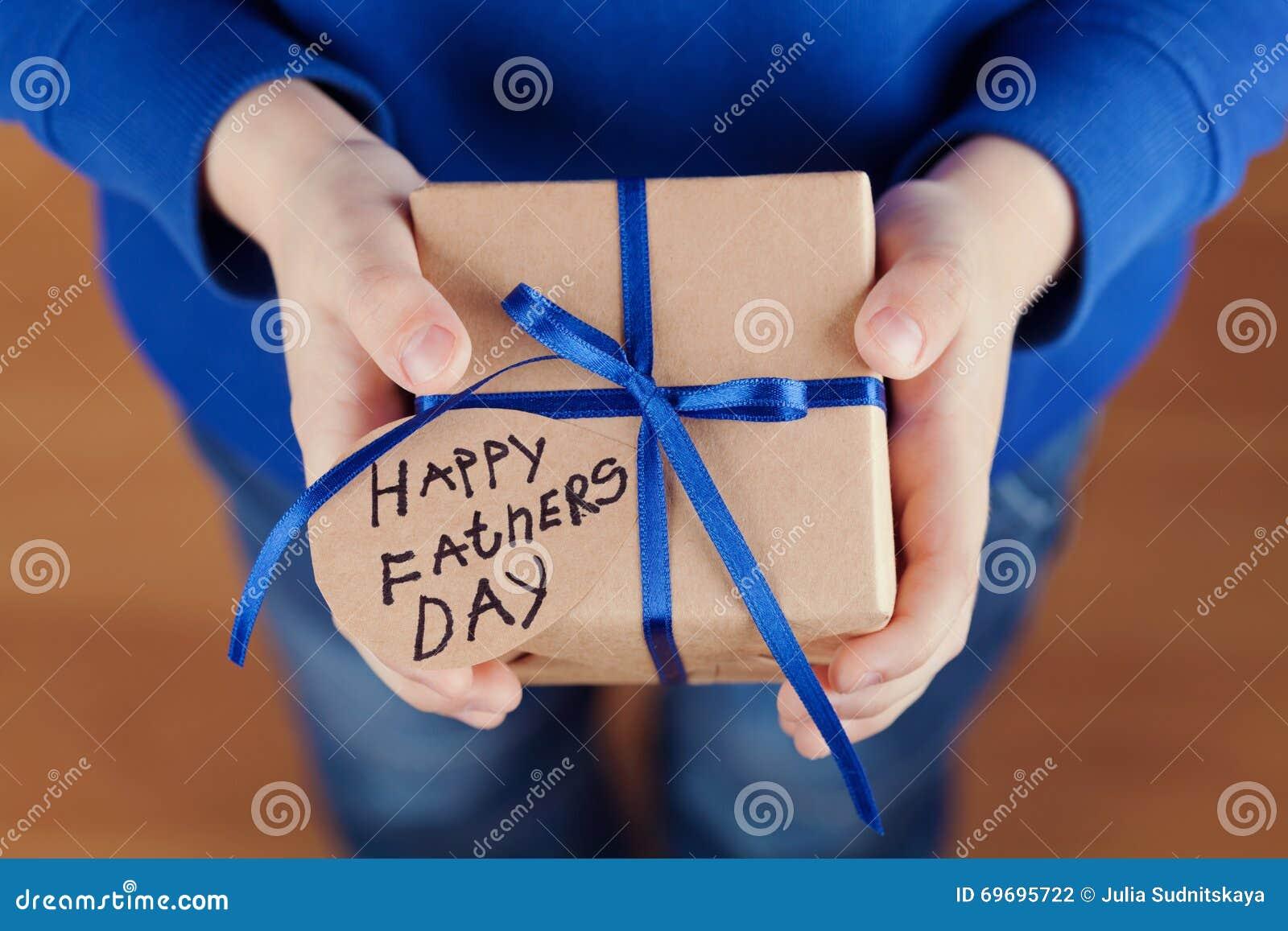 Die Hände der Kinder, die ein Geschenk oder einen Präsentkarton mit Kraftpapier halten und gebundenes Tag des blauen Bandes am gl
