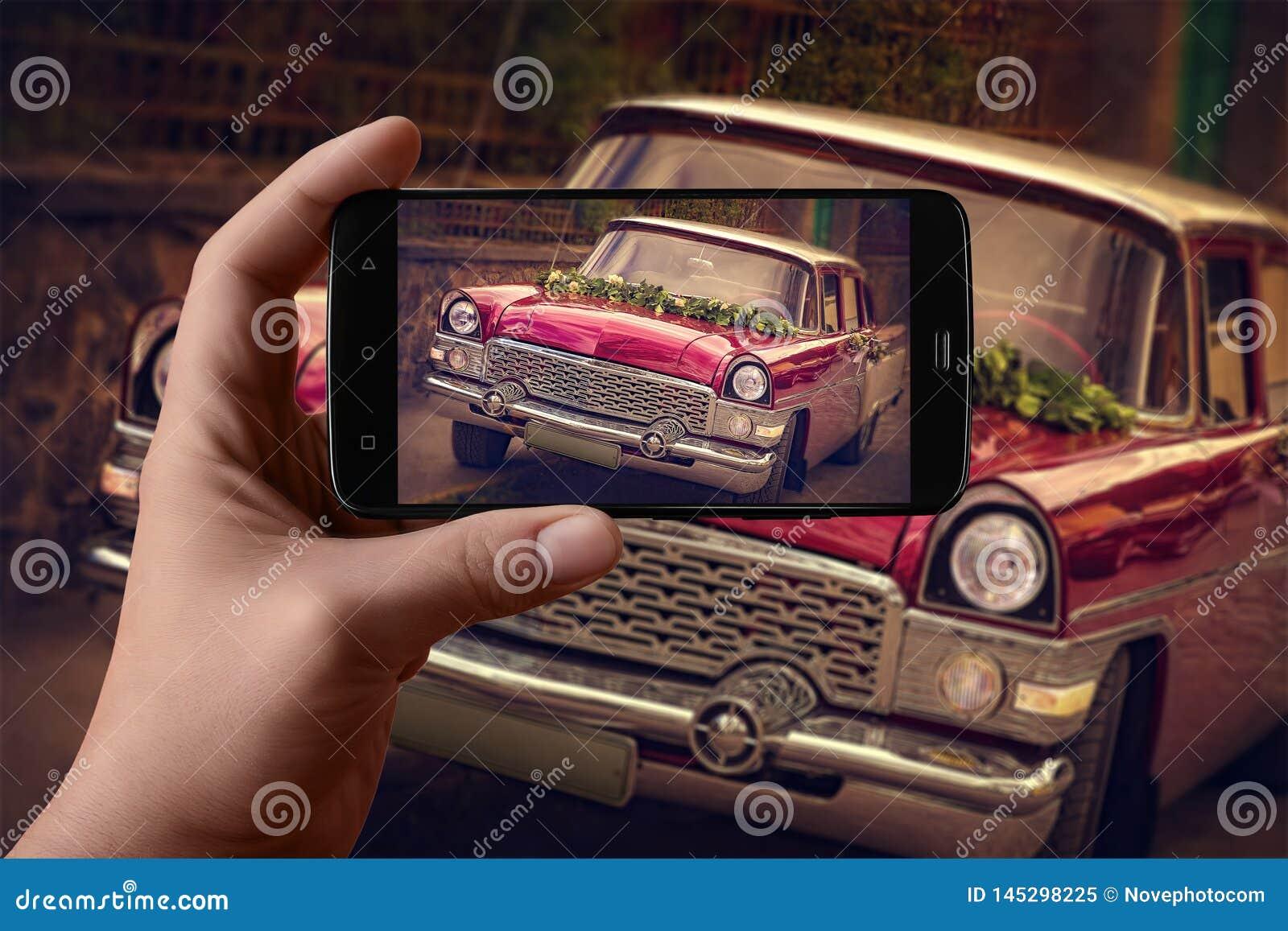 Die Hände der Männer, die Fotos des Autos am Telefon machen Festliches Auto der Weinlese