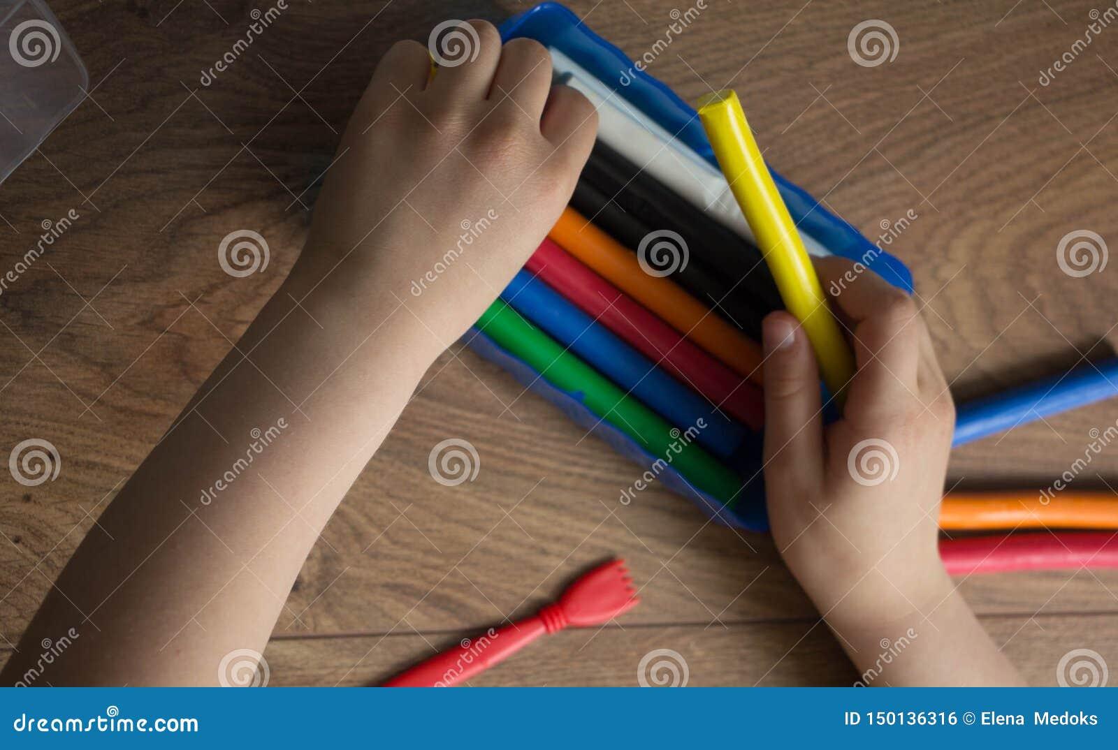 Die Hände des kleinen Mädchens den mehrfarbigen Lehm herausnehmen