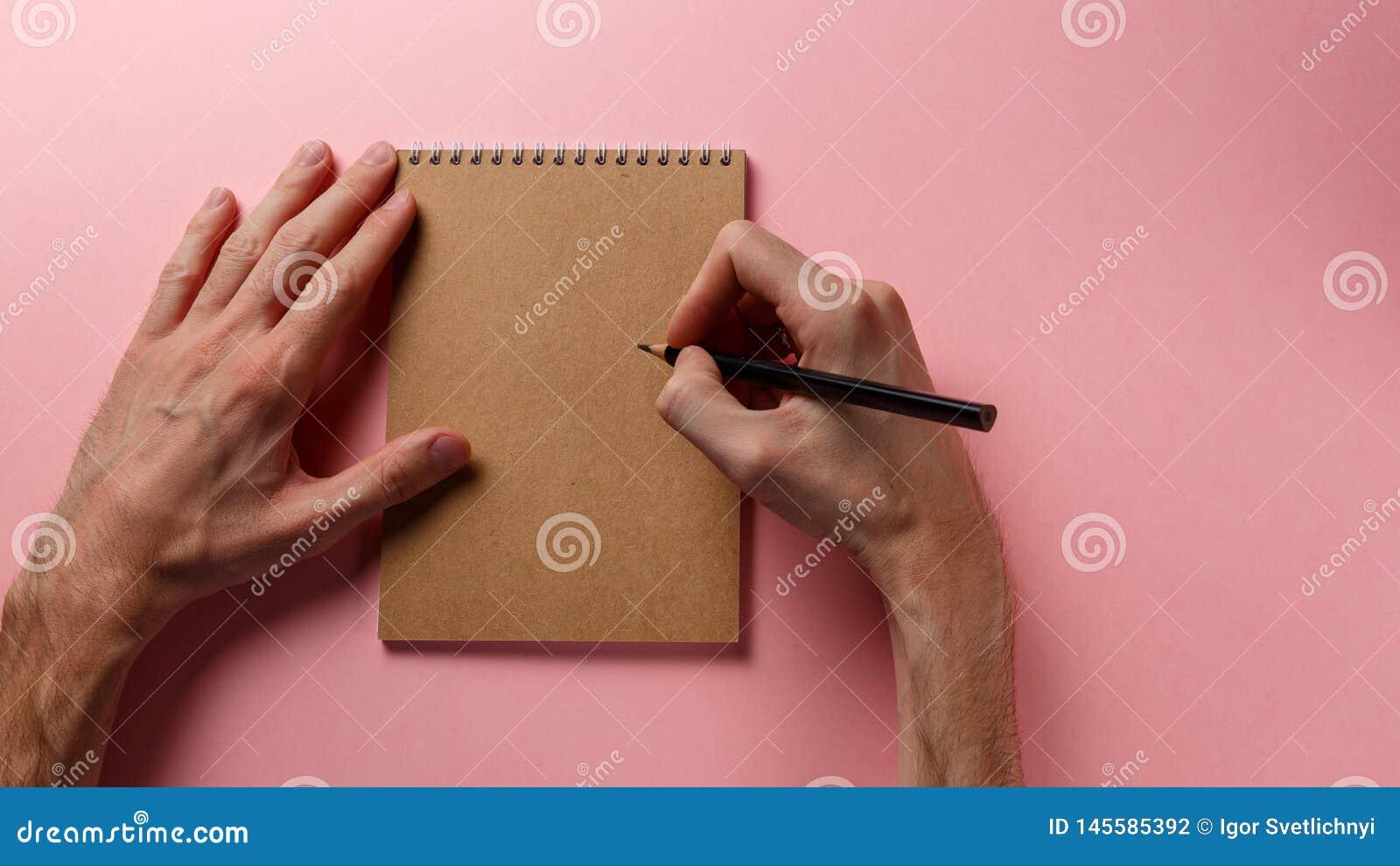 Die Hände des Mannes, die Bleistift und Spiralennotizblock halten