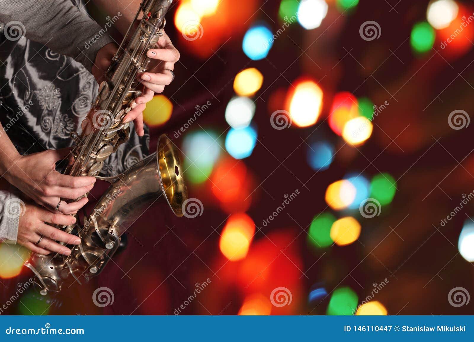 Die Hände des Mannes und der Frau mit Saxophon auf bokeh Lichtern