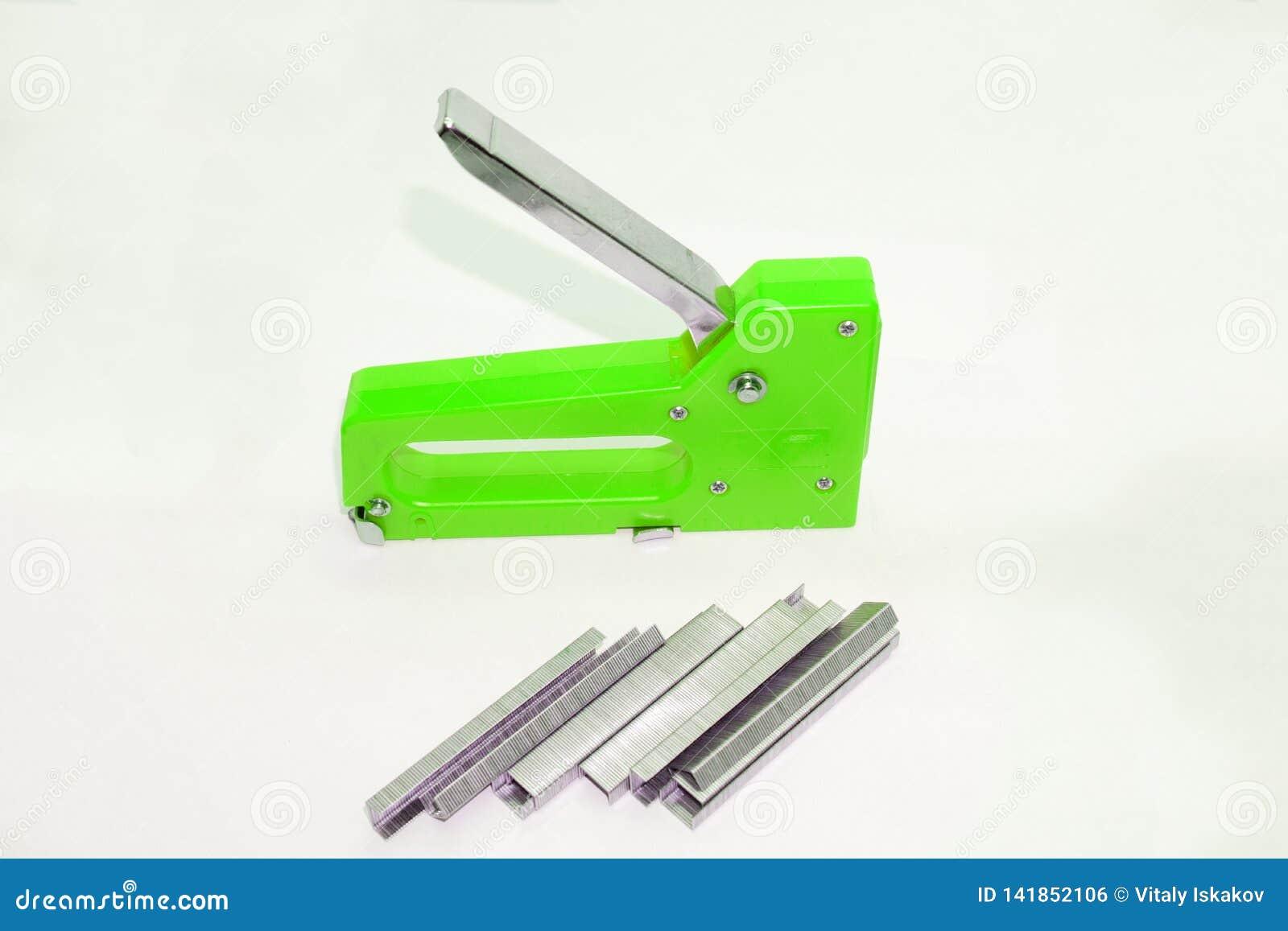 Die Hand der Arbeitskraft benutzt einen industriellen Stahlhefter industrieller Hefter, der das Leder auf das Holz durch die Heft