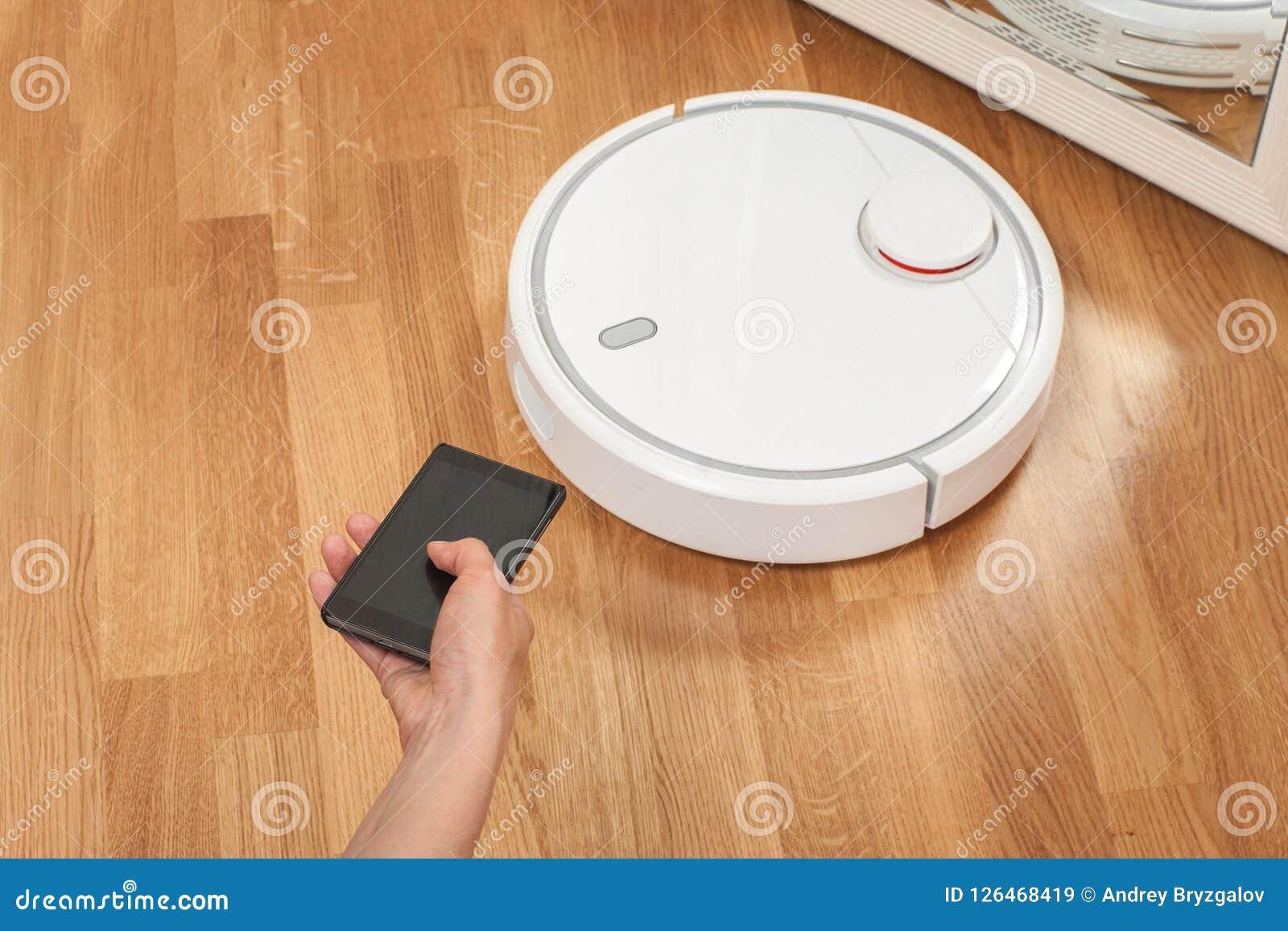 Die Hand der Frauen unter Verwendung des Mobiles, zum des weißen Roboterstaubsaugers zu steuern moderne intelligente Reinigungste