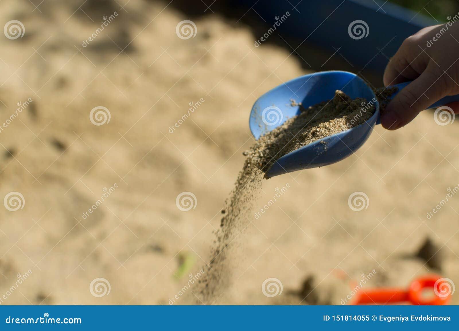 Die Hand der Kinder gießt Sand mit einer blauen Schaufel