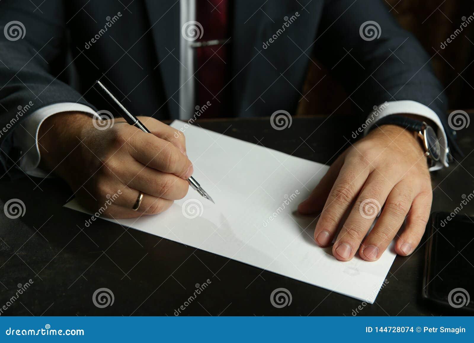 Die Hand des Geschäftsmannes schreibt mit Füllfederhalternahaufnahme