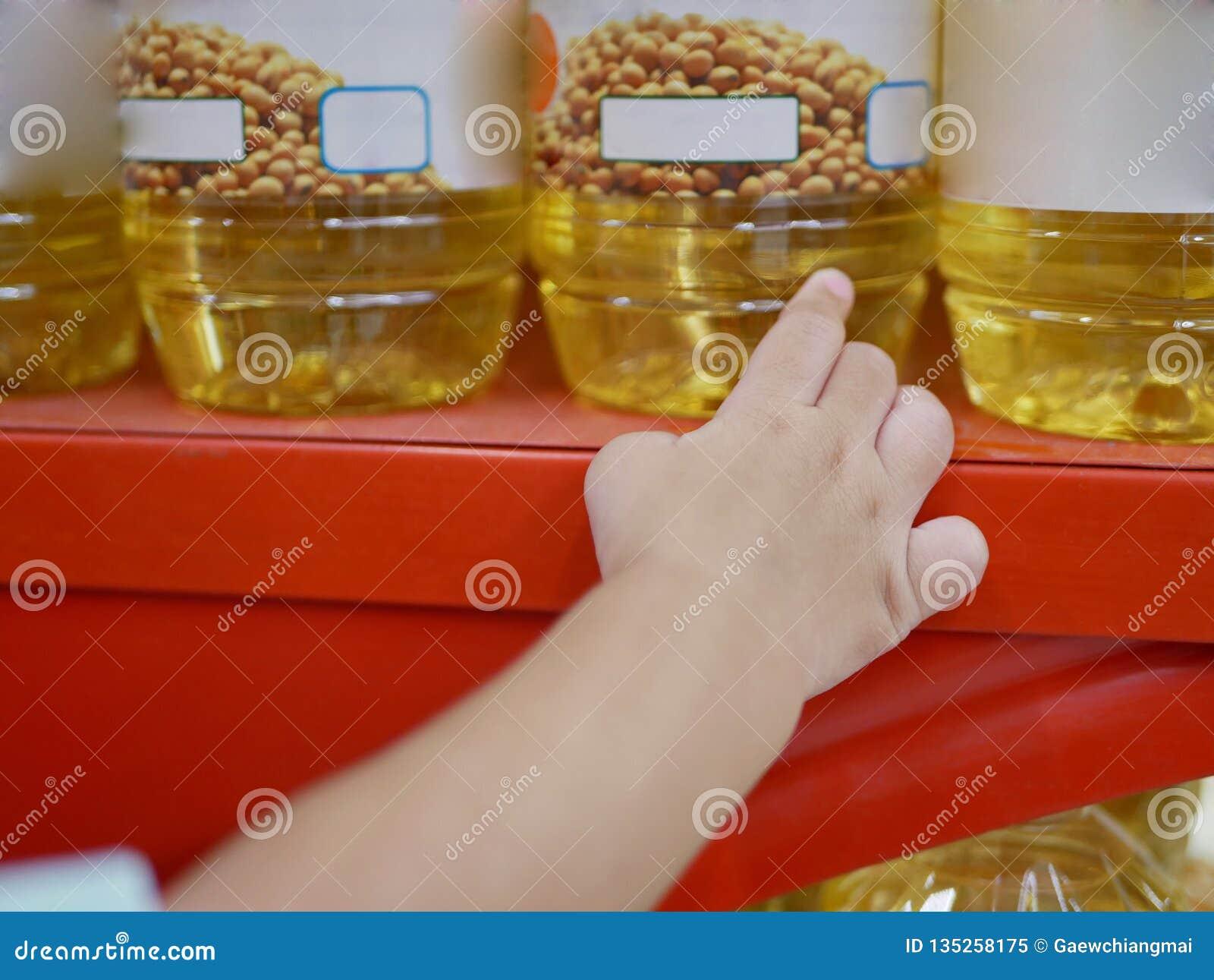 Die Hand des kleinen Babys, die eine Flasche Speiseöl auf nimmt beiseite zu legen