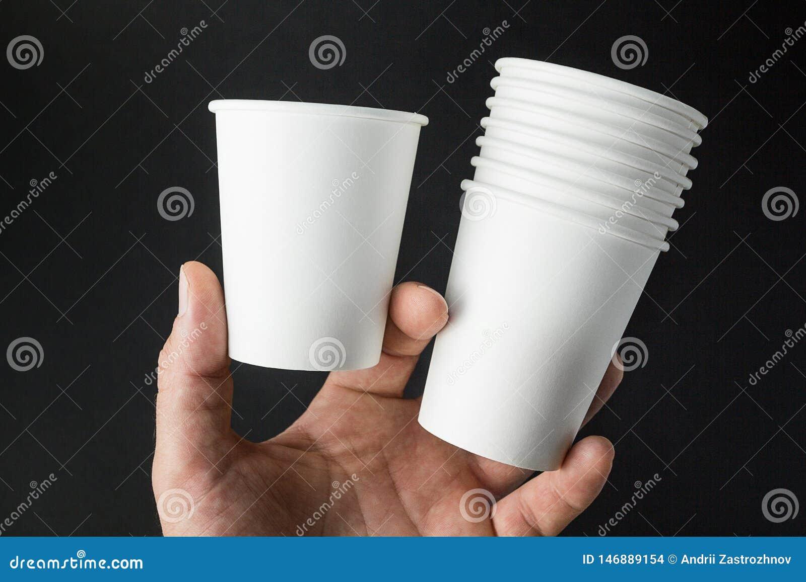 Die Hand eines Mannes hält Modelle von Schalen für Kaffee, Tee, Soda und Saft auf einem schwarzen Hintergrund