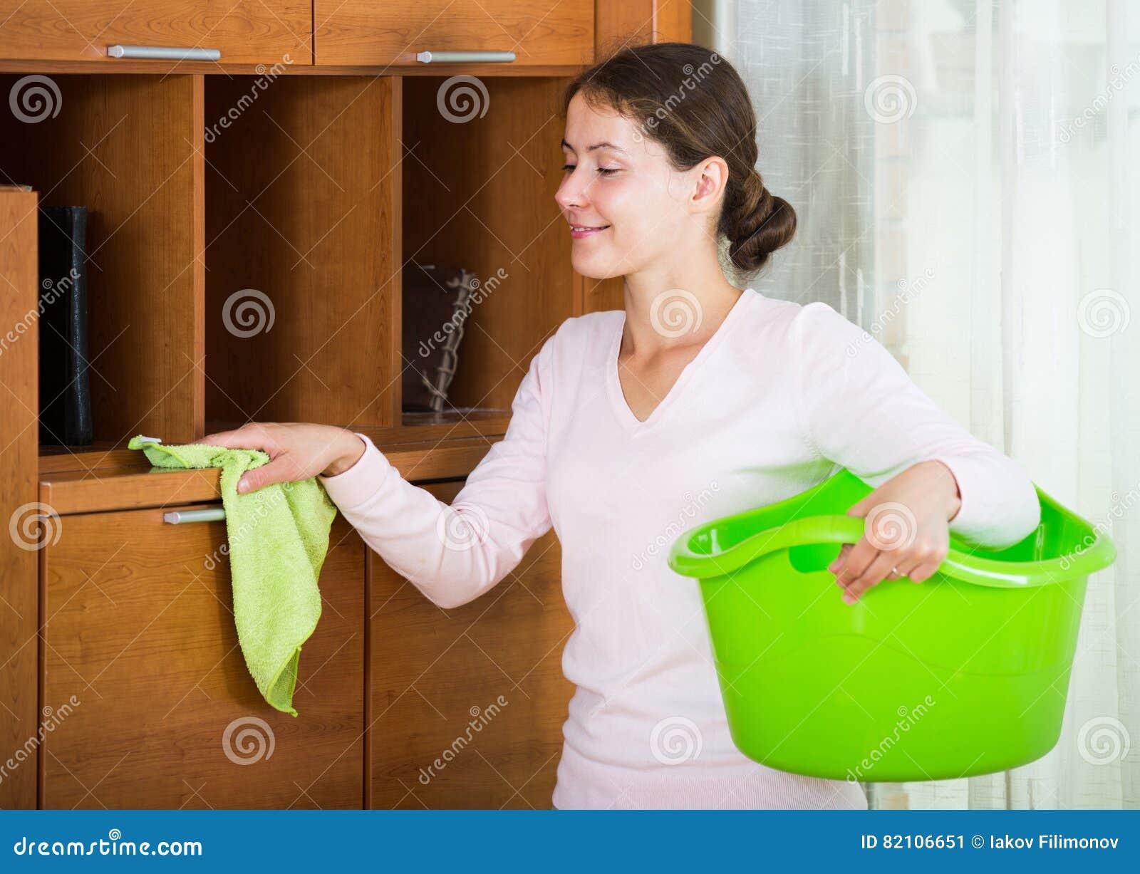 Die Hausfrau, die Regular tut, räumen in Wohnzimmer auf