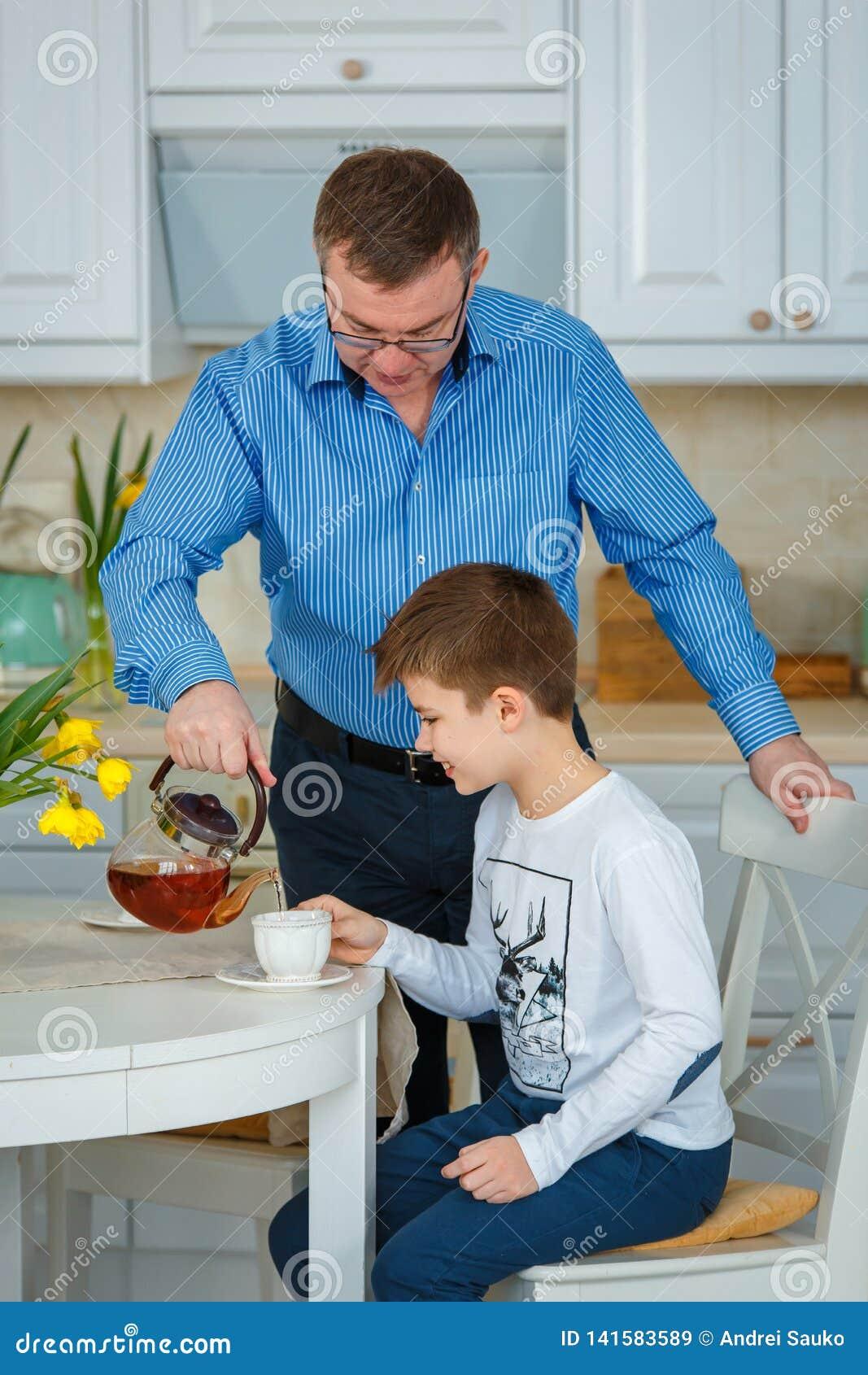 Die helle Teeschale mit einem heißen Getränk Vater gießt Tee