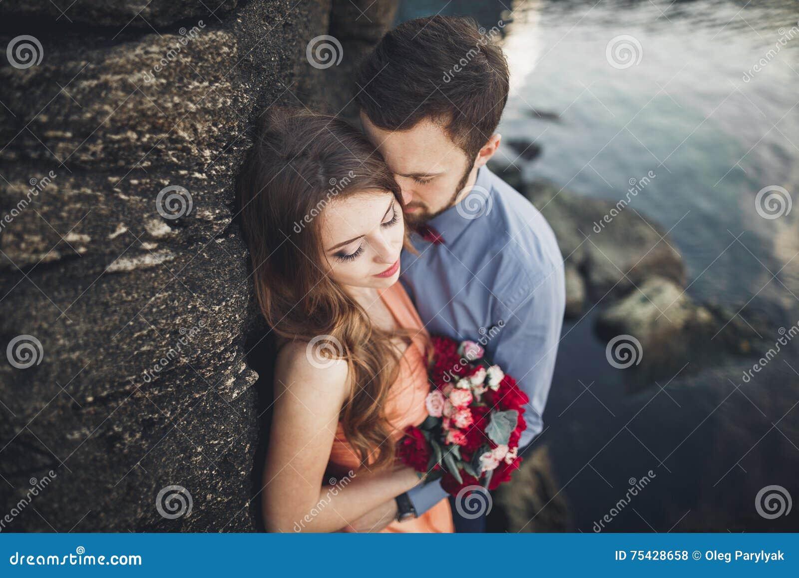 Die Hochzeitspaare, die auf Felsen küssen und umarmen, nähern sich blauem Meer