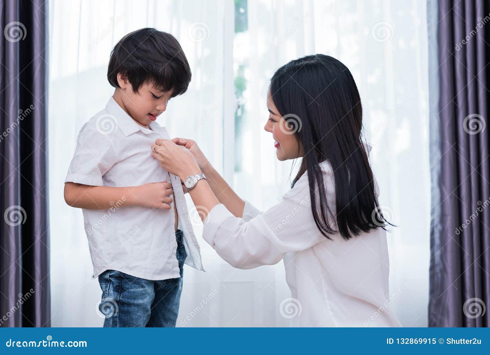 Die junge asiatische Mutter, die herauf Sohnausstattungen für das Vorbereiten gekleidet wird, gehen zu schulen Mutter- und Sohnko