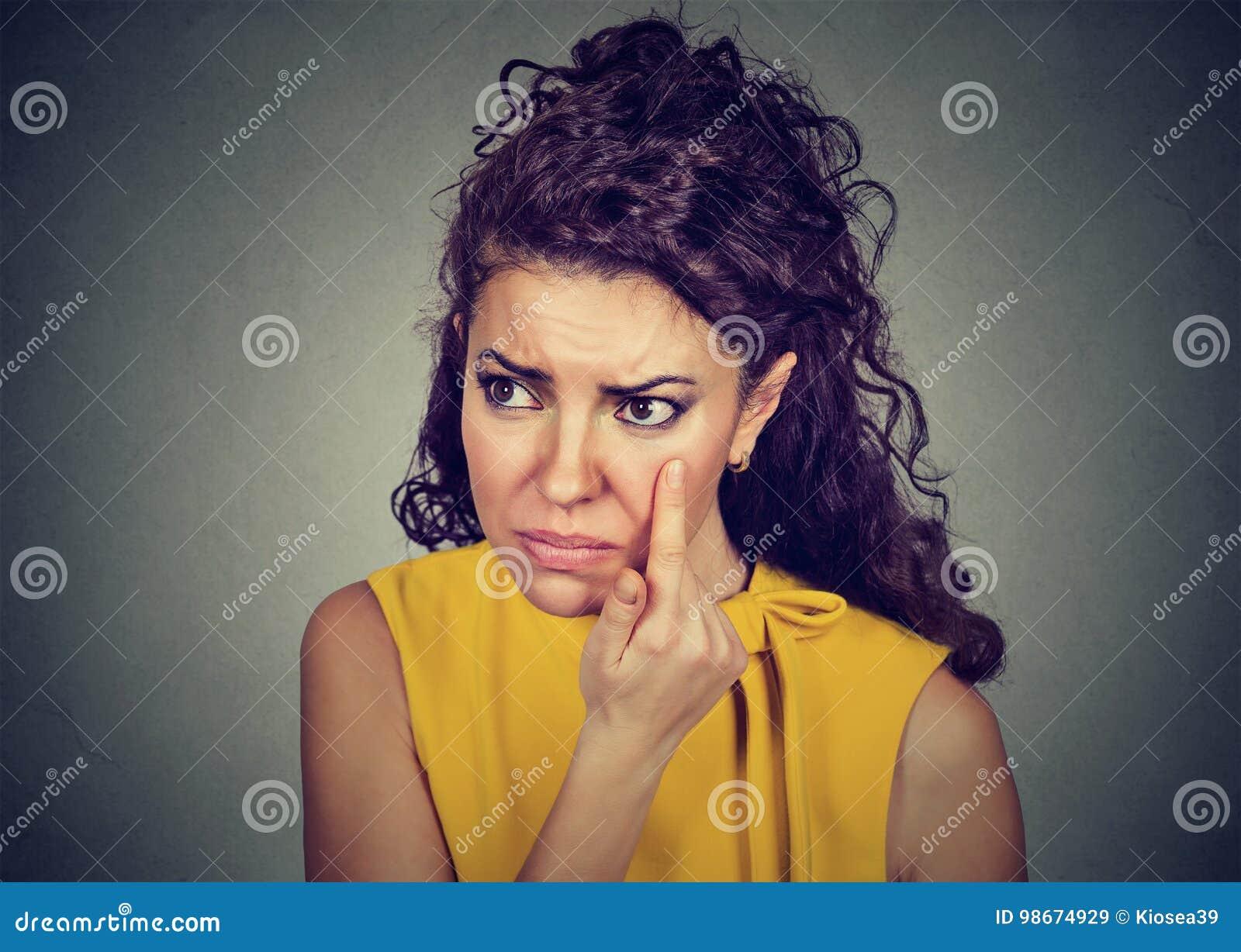 Die junge Frau, die hinunter das Augenlid überprüft ihr Auge schaut im morgigen Tag zieht, glaubt, dass unwohl schwarze Kreise ha