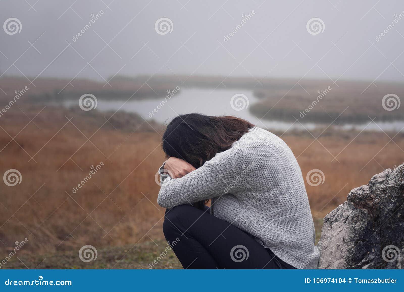 Die junge Frau, die an einem Stein mit den Armen sich lehnt, kreuzte vor dem Gesichtsschreien