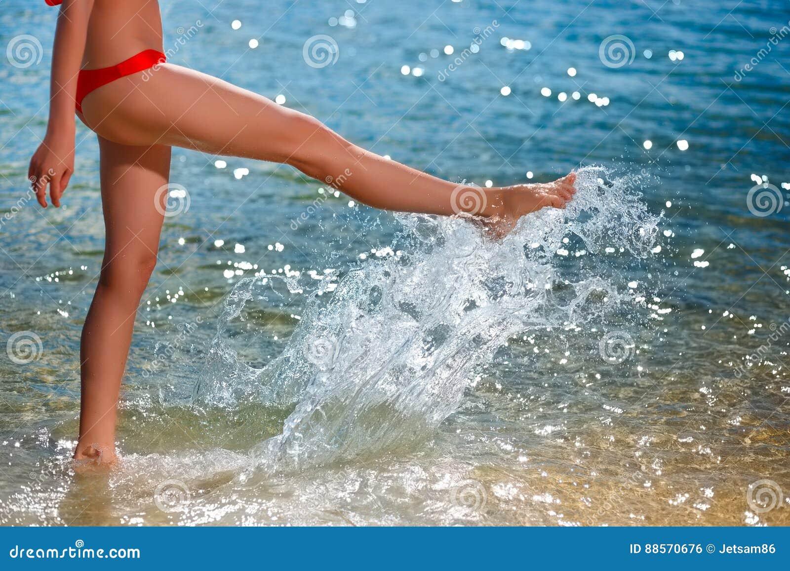 Die junge Schönheit, die auf den Strand geht und spritzt Wasser vorbei