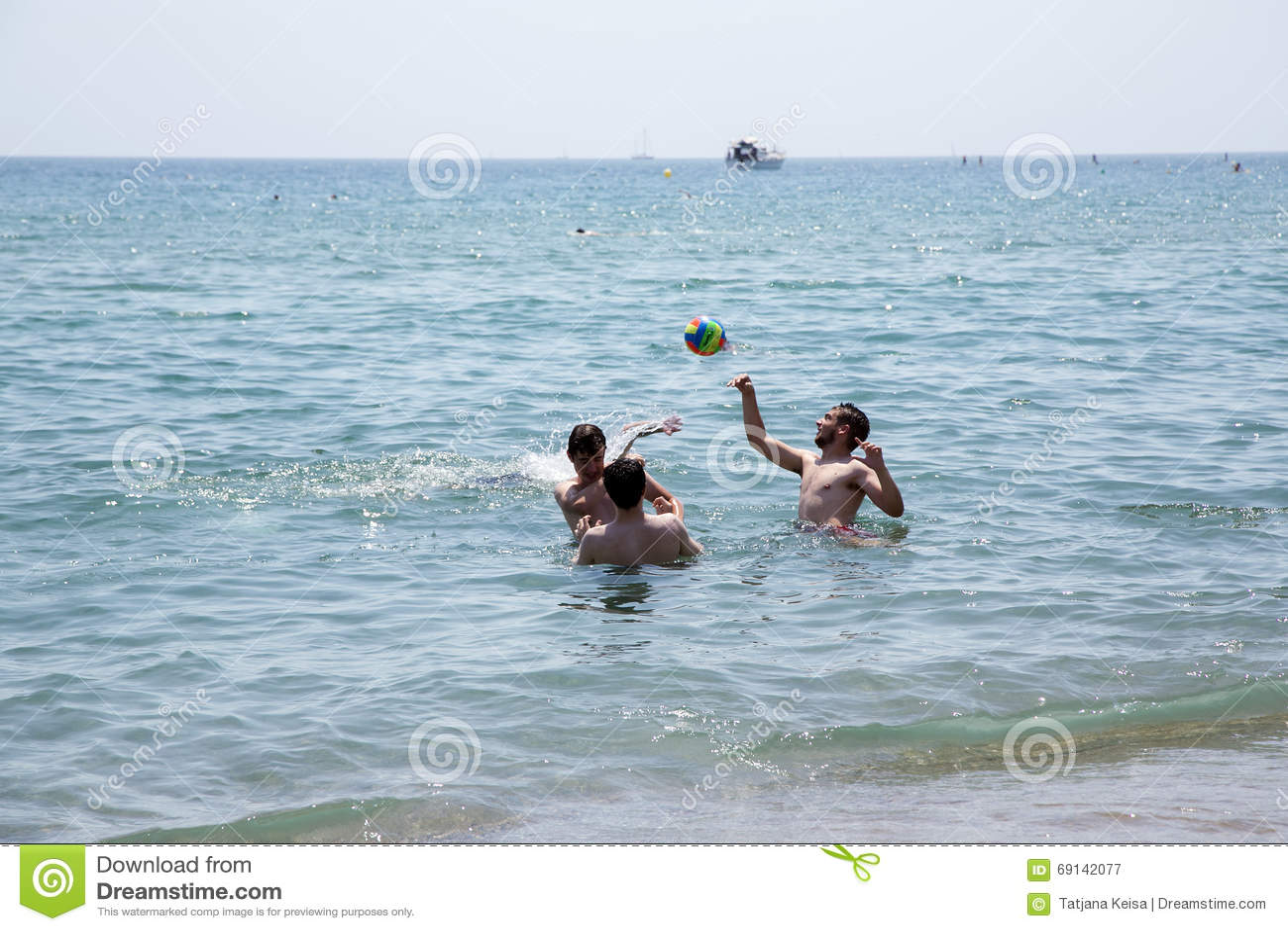 die jungen die mit einem ball im wasser auf dem barcelonetta spielen setzen auf den strand. Black Bedroom Furniture Sets. Home Design Ideas