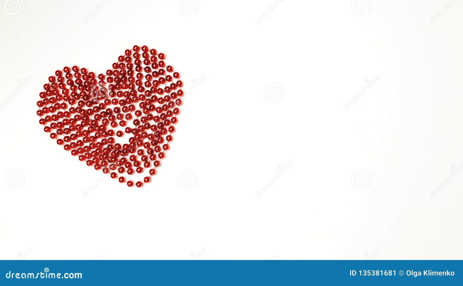 Die Kette von den roten Bällen gefaltet in Form eines Herzens - ein Symbol aller Liebhaber und Valentinstags