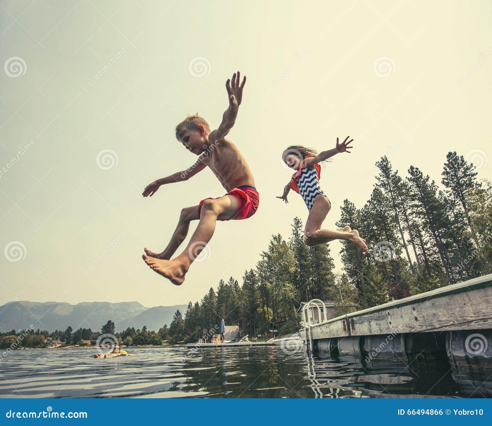 Die Kinder springend weg vom Dock in einen schönen Gebirgssee