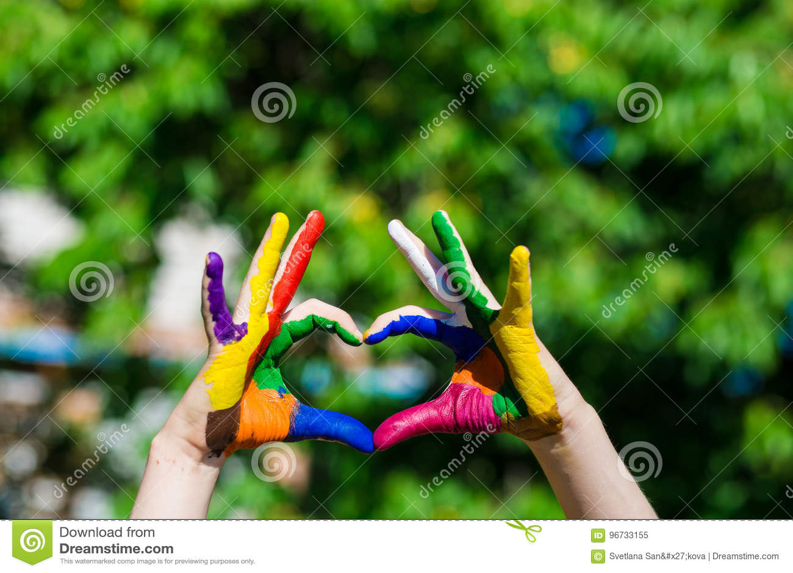 Die Kinderhände, die in den hellen Farben gemalt werden, machen eine Herzform auf Sommernaturhintergrund