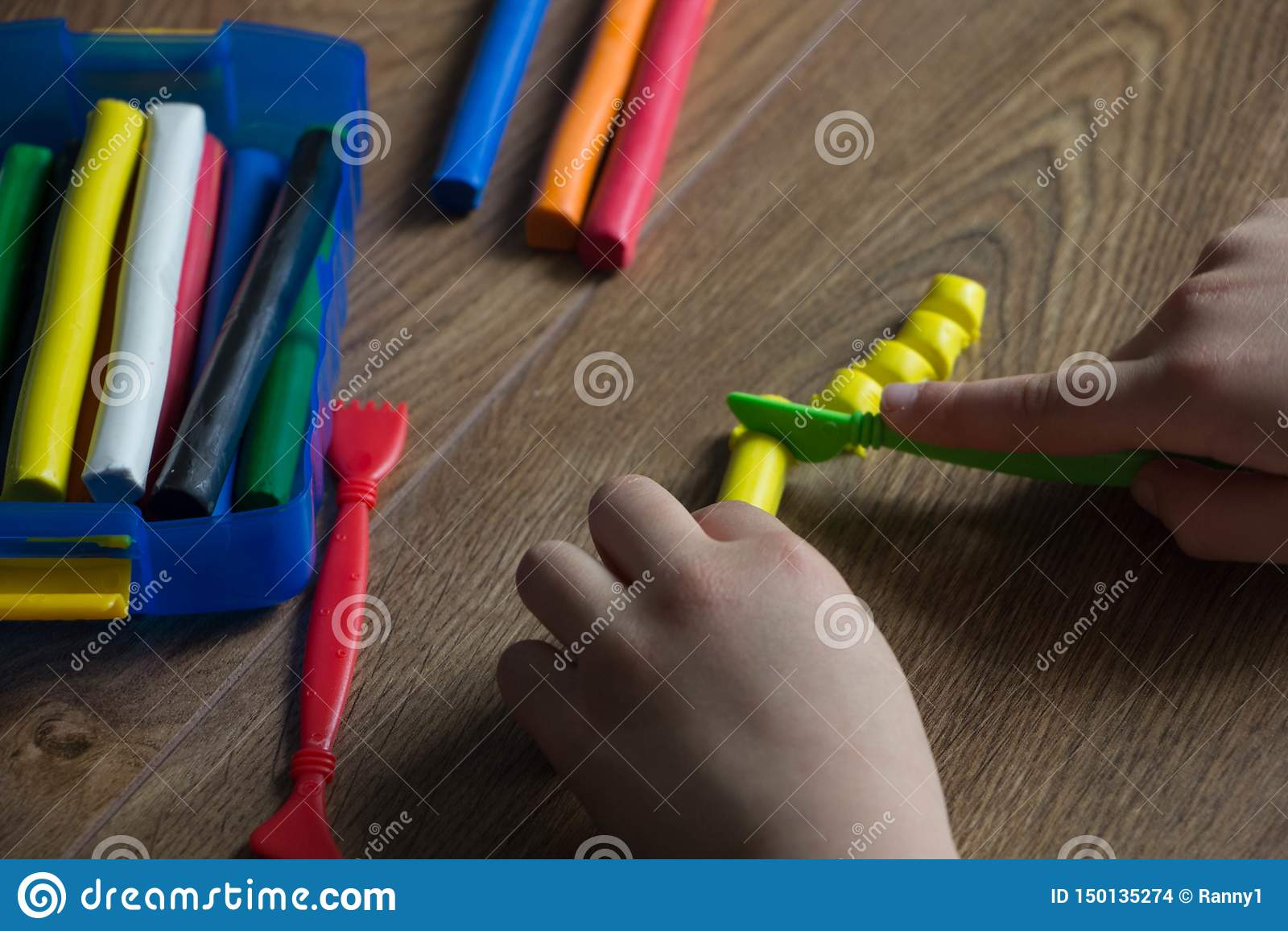 Die Kinderspiele in einem mehrfarbigen Plasticine auf einem Holztisch Kreativ mit Kindern