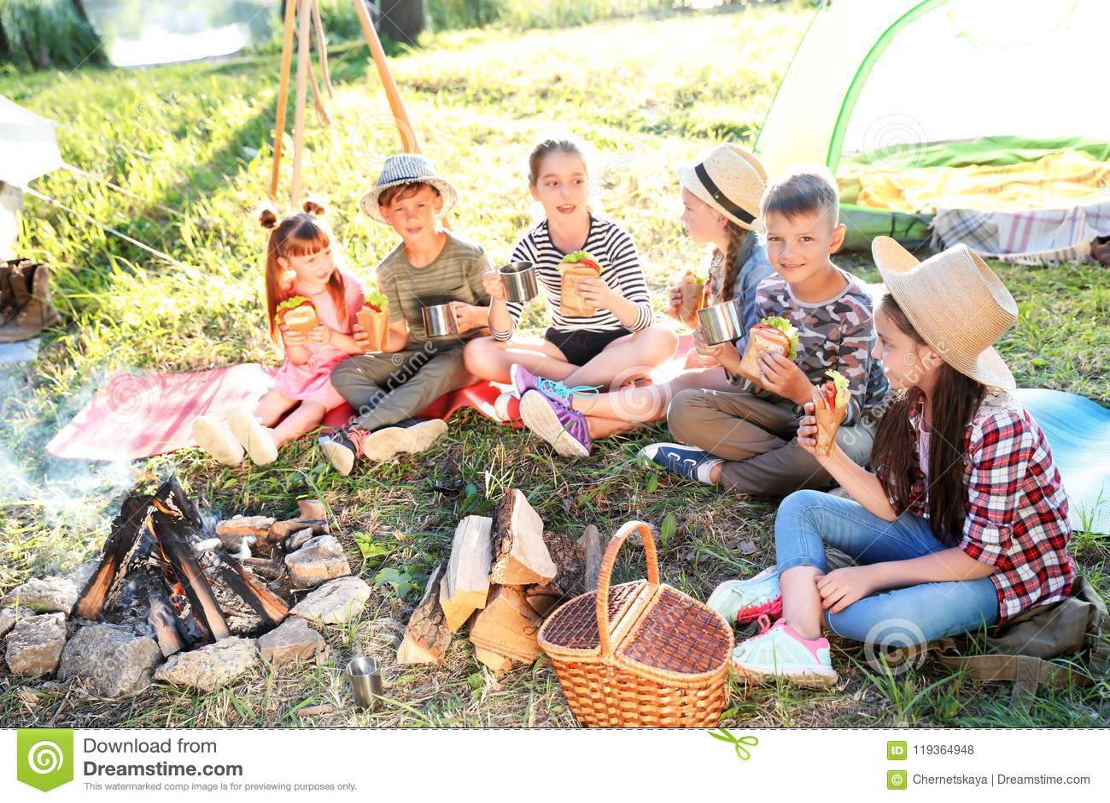 Die kleinen Kinder, die Sandwiche essen, nähern sich Feuer