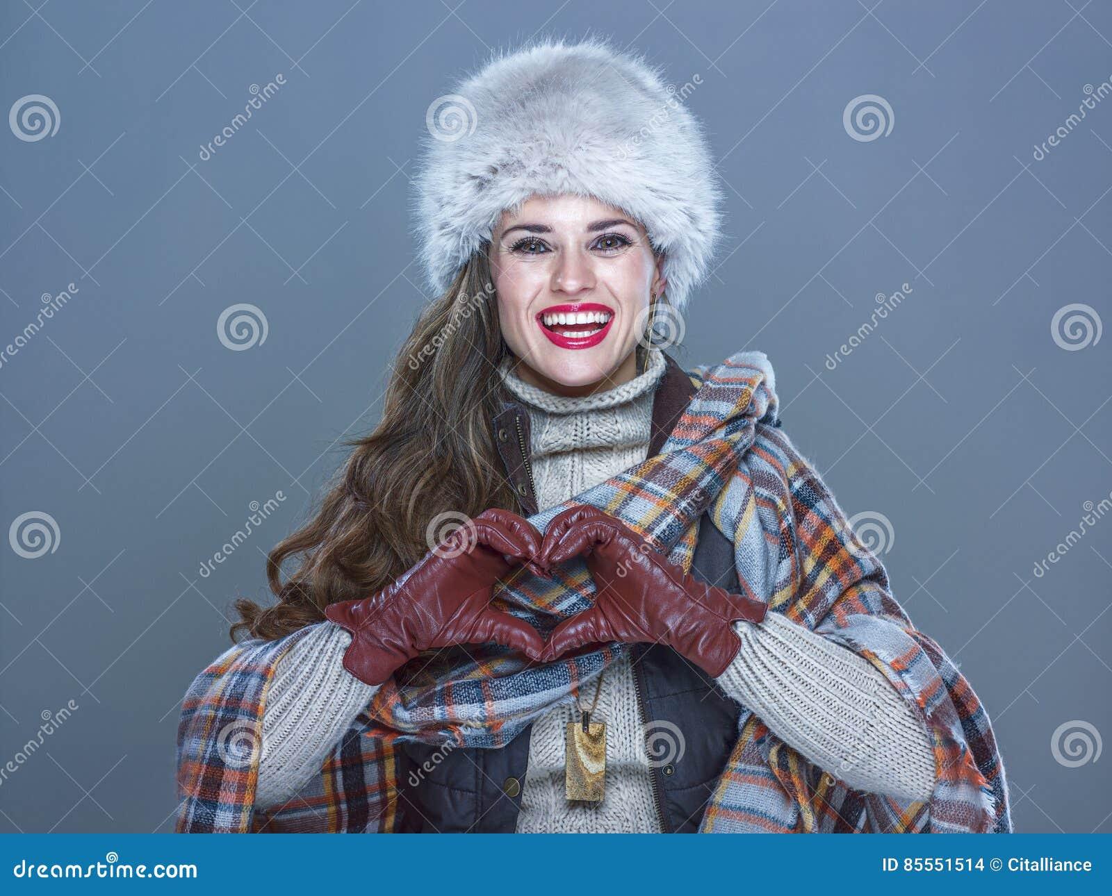 Die lächelnde Frau, die auf kaltem blauem darstellendem Herzen lokalisiert wurde, formte Hände