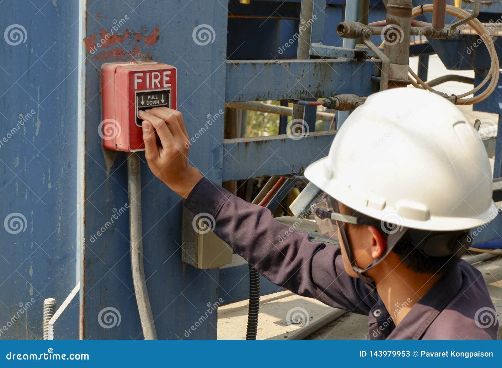Die Männer, die Schutzhelme tragen, bedrängen Feuermelder