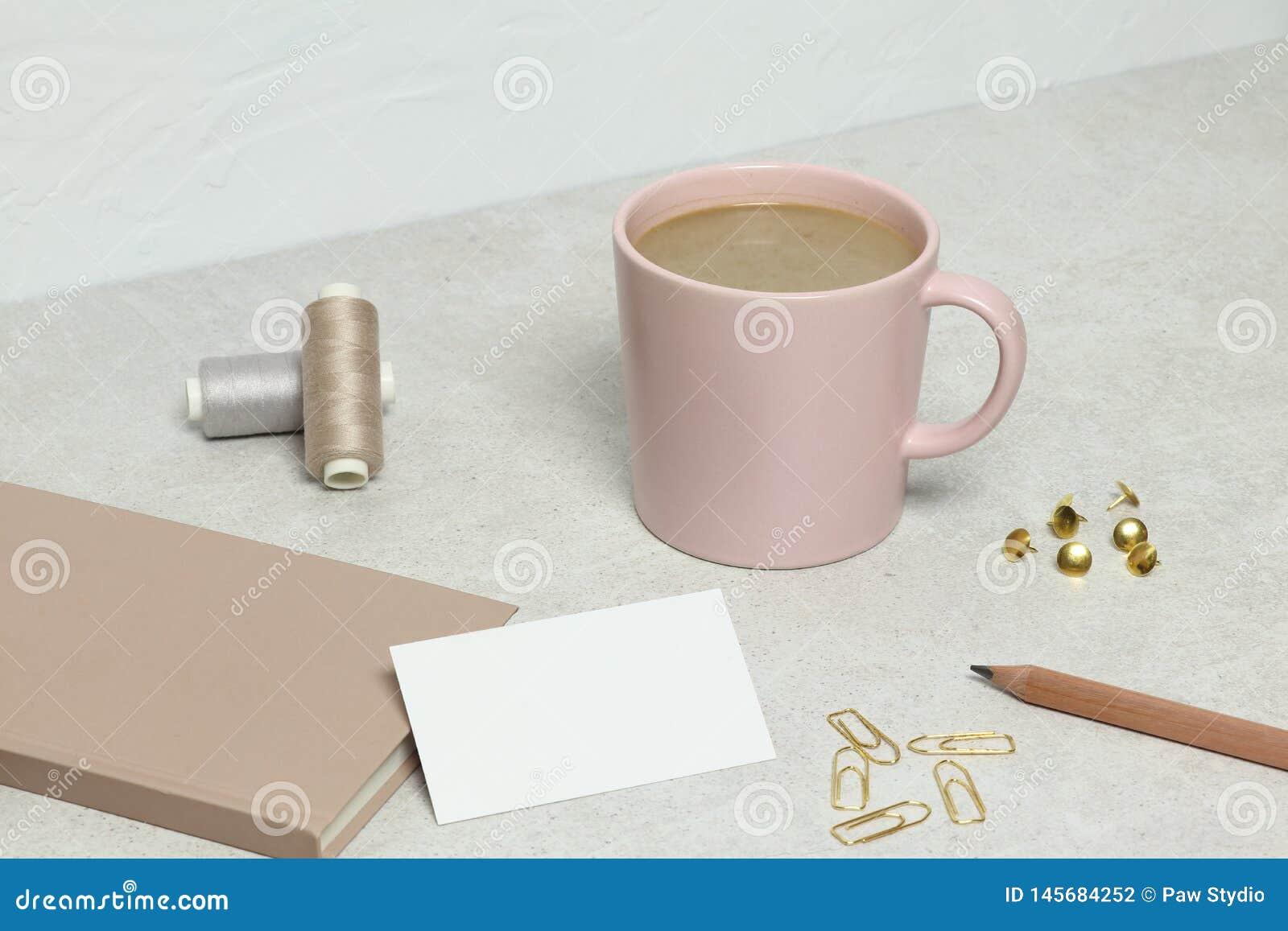 Die Modellvisitenkarte, das Buch, der Bleistift, die Büroklammern, die Stifte und die Faden, Tasse Kaffee auf Granitbeschaffenhei
