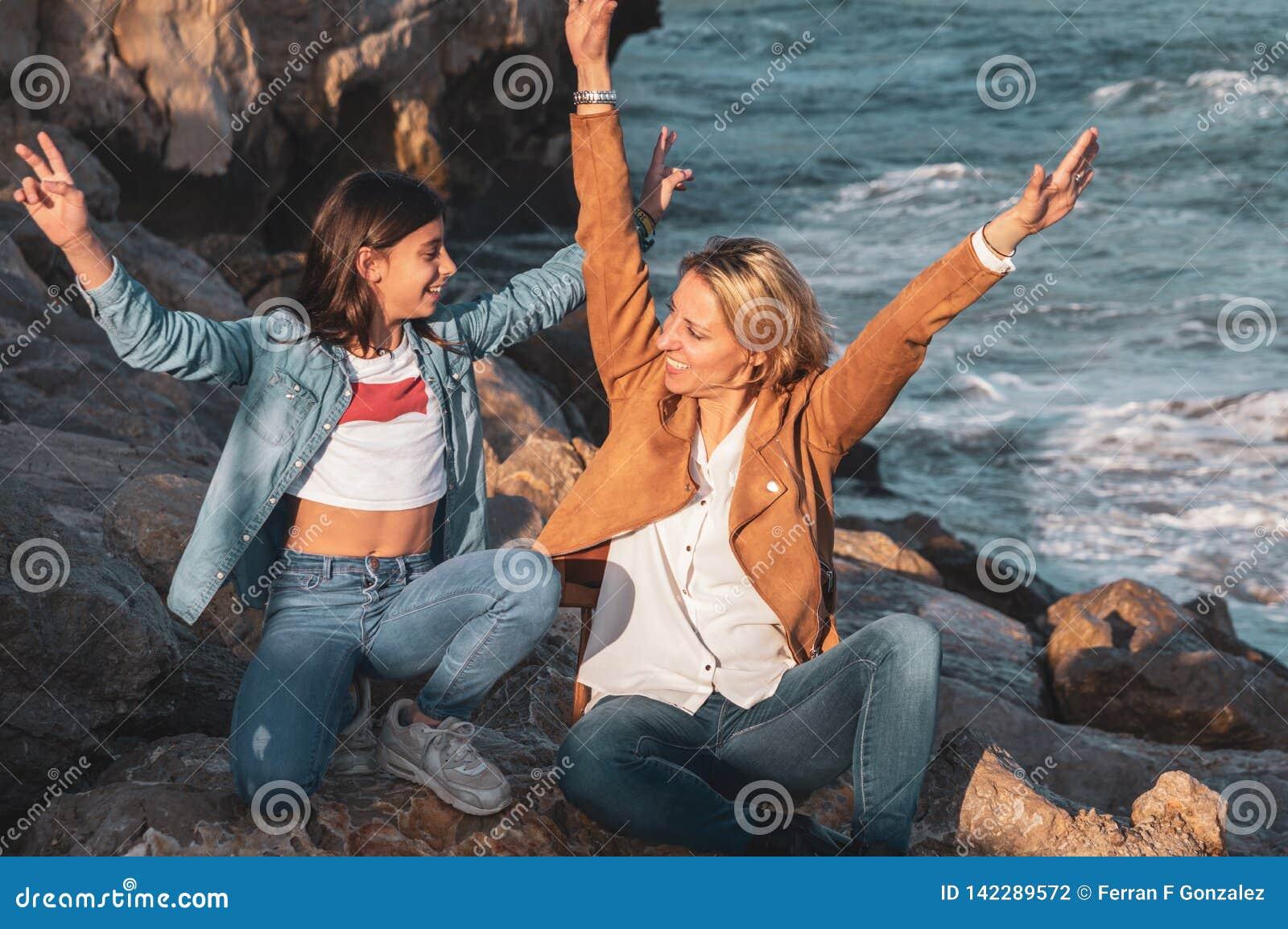 Die Mutter und Tochter, die auf dem Rock durch das Mittelmeer mit den Armen sitzen, hoben das Spielen mit der Luft an