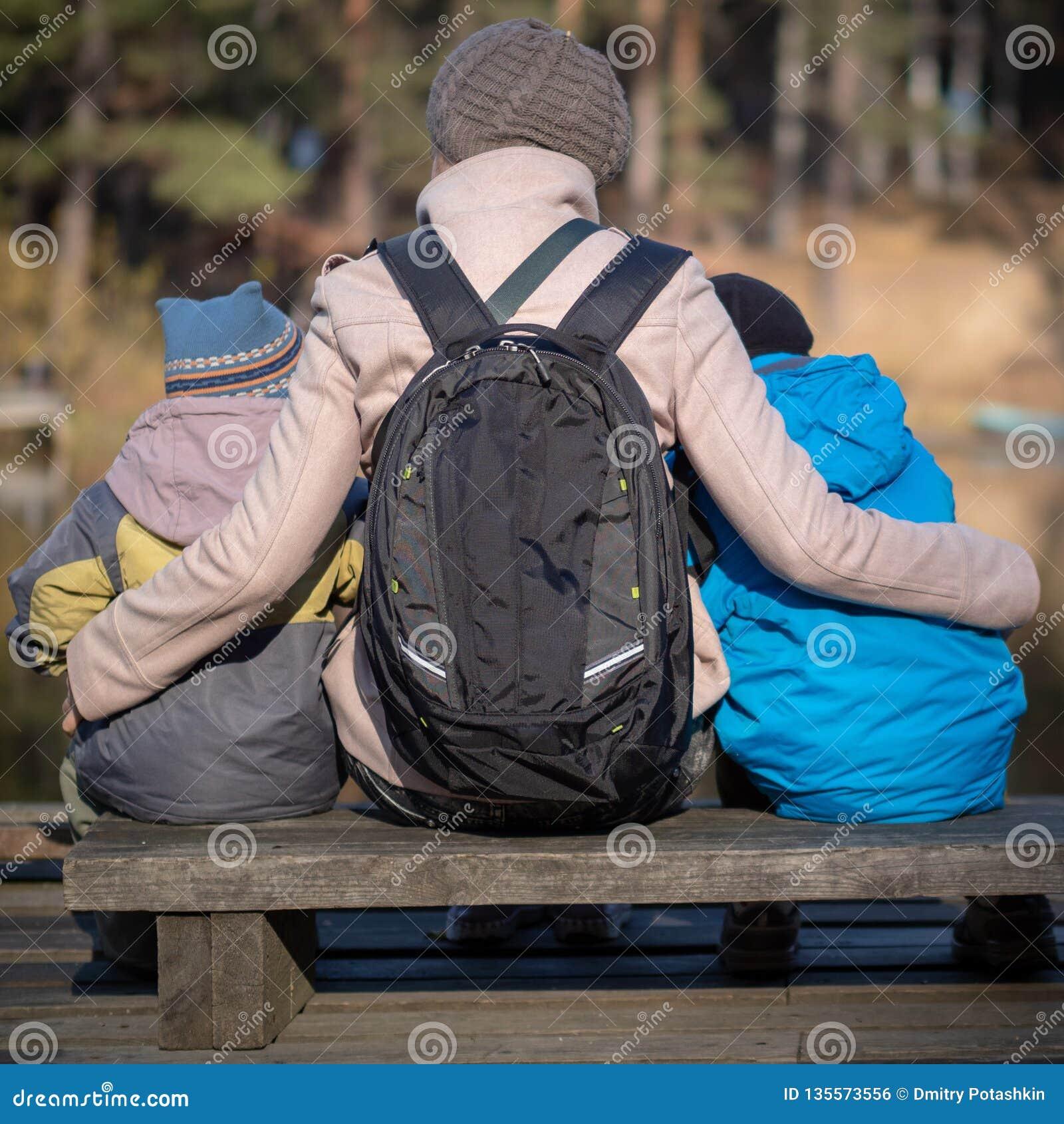 Die Mutter von zwei jungen Söhnen sitzen auf einer Parkbank