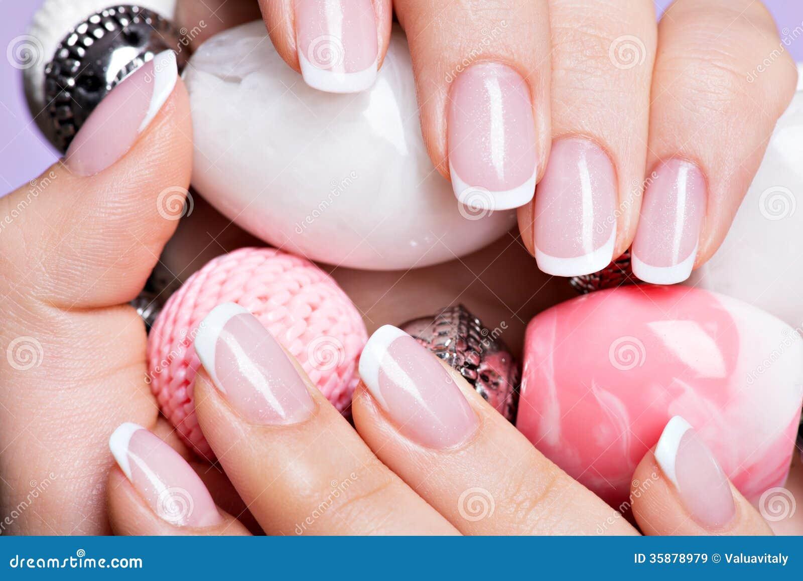Die Nägel der Frau mit schöner französischer weißer Maniküre