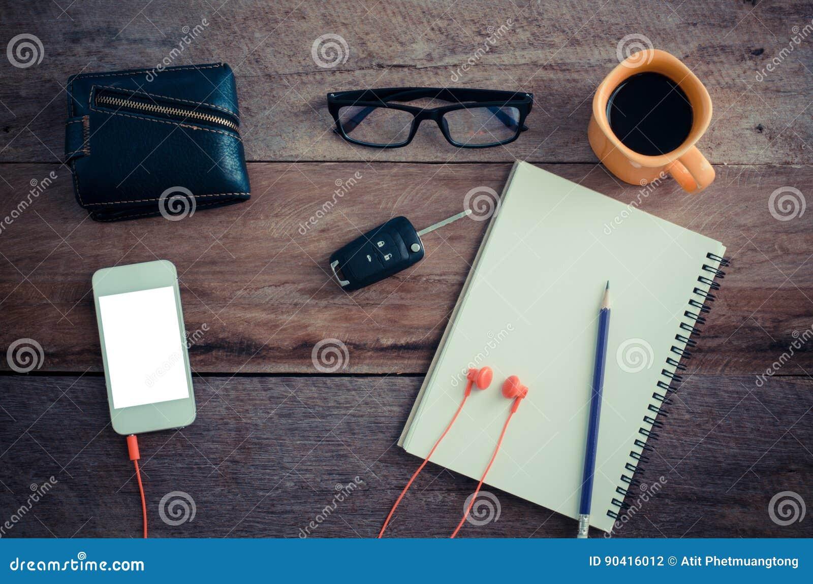 Die Oberfläche eines Holztischs mit einem Notizbuch, Smarttelefon, Gläser, Geldbörse, Autoschlüssel, Kaffeetasse