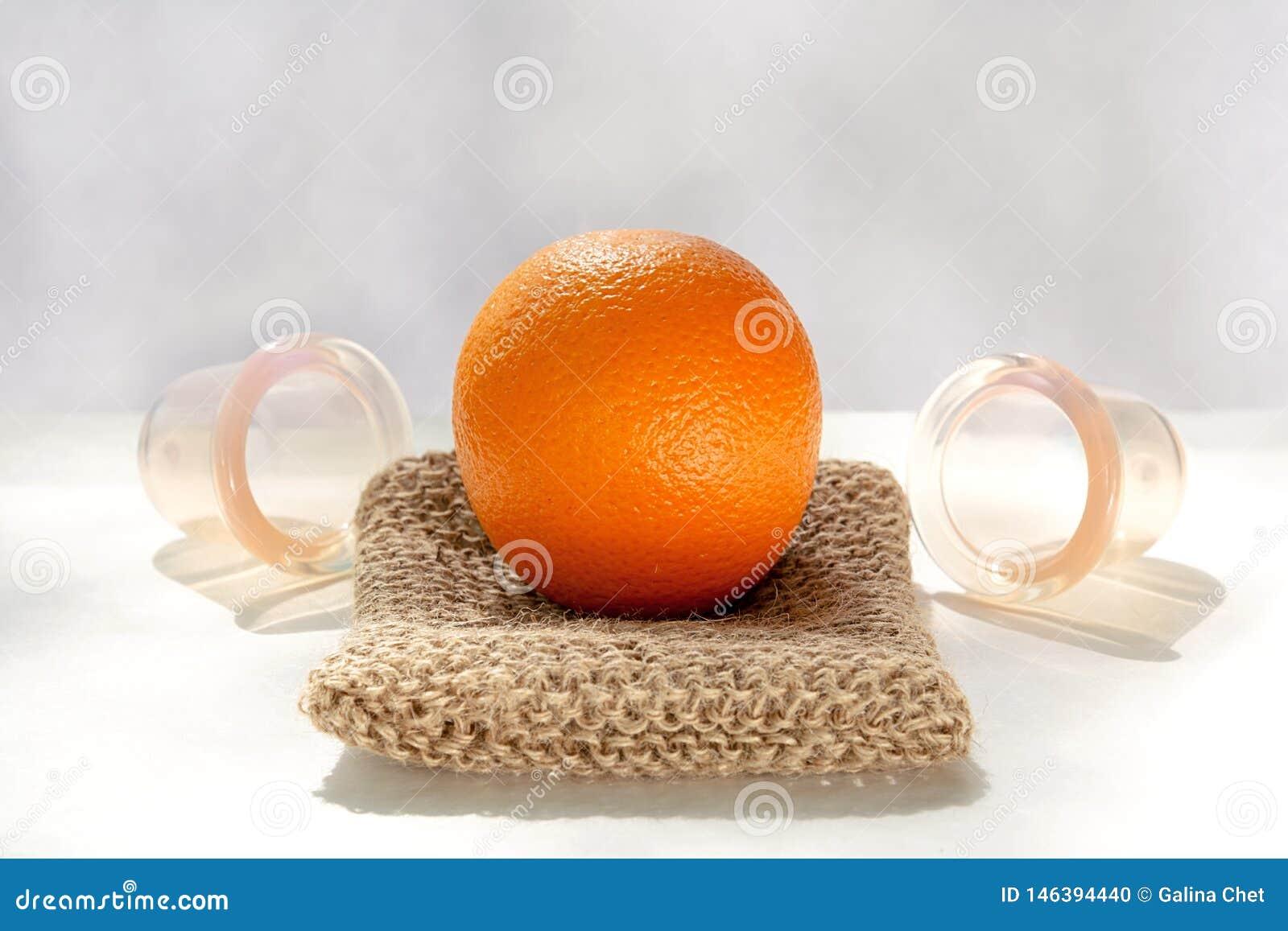 Die orange L?gen auf einem Maschenwaschlappen, der von den Naturfasern und nahe bei ihm gemacht wird, sind Vakuumbanken