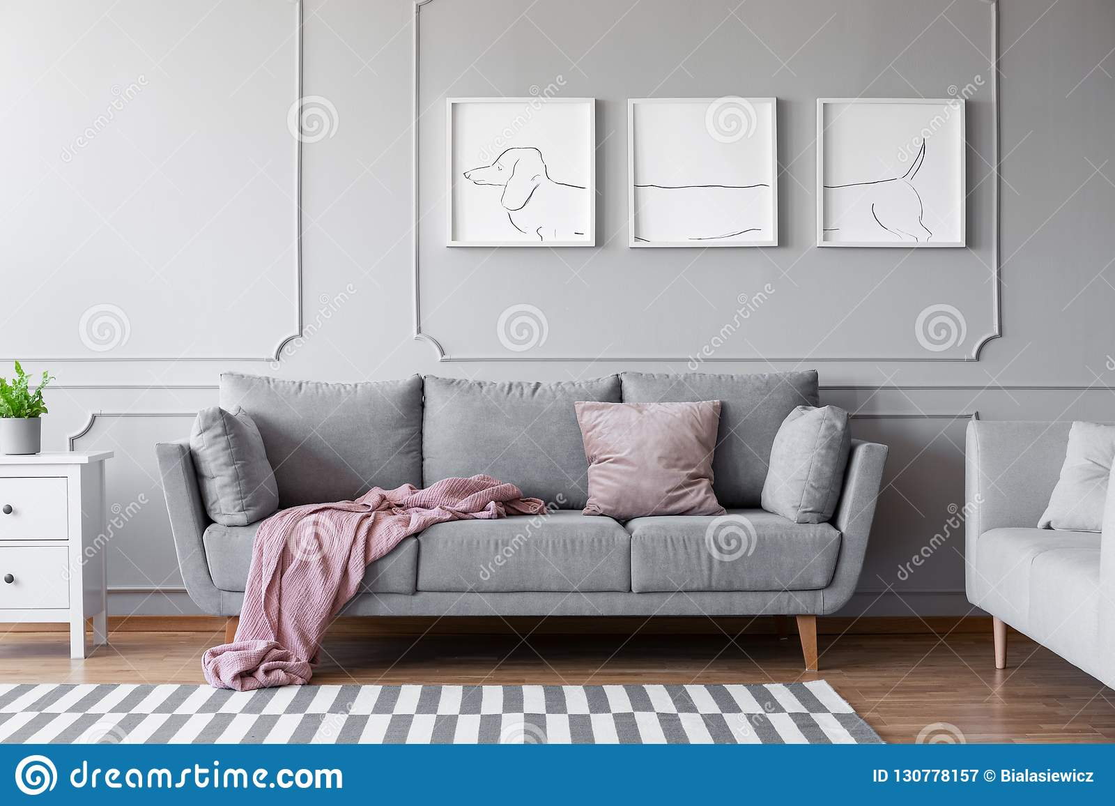 Die Plakate des Hundes über bequemer grauer Couch im stilvollen Wohnzimmerinnenraum mit zwei Sofas