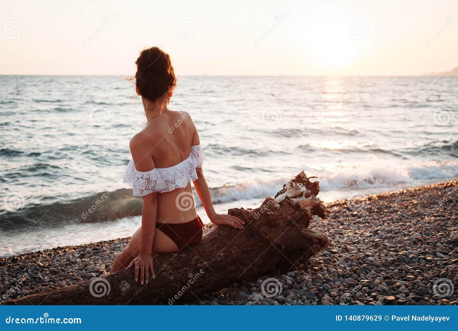 Die schöne junge Frau, die auf Strand bei Sonnenuntergang sitzt und meditiert