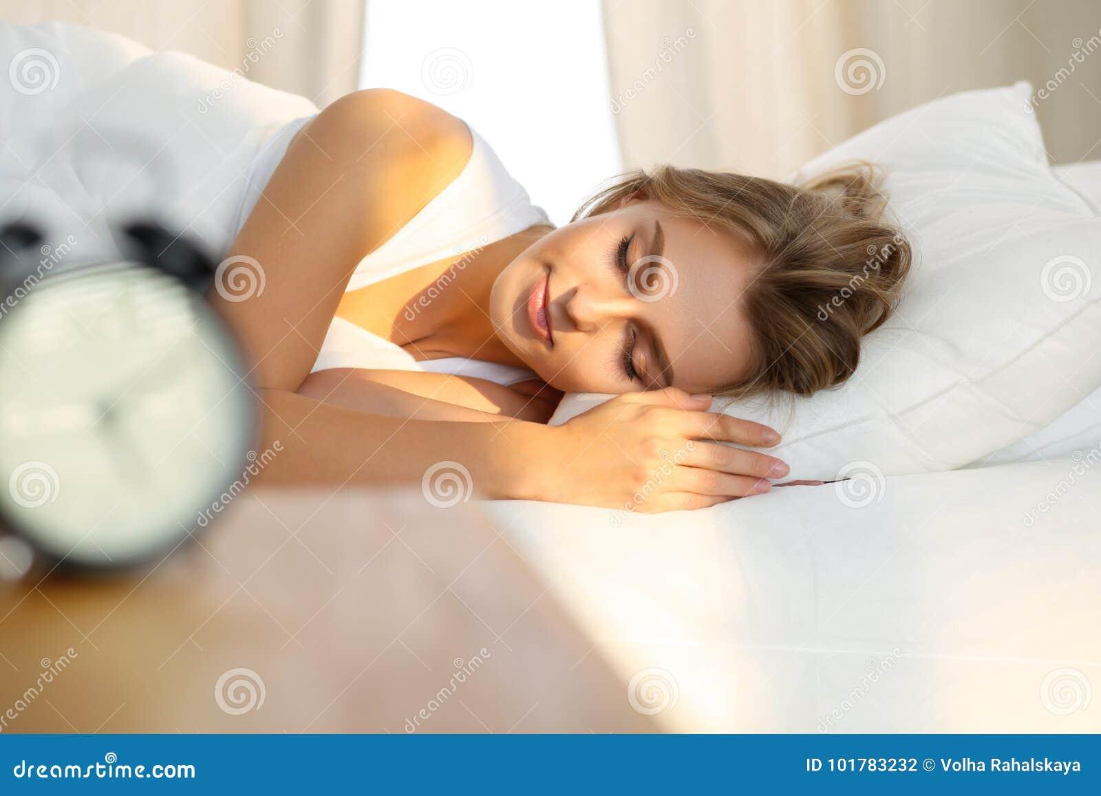 Die schöne junge schlafende Frau, beim im Bett bequem liegen und himmlisch Sonnenstrahl dämmern auf ihrem Gesicht