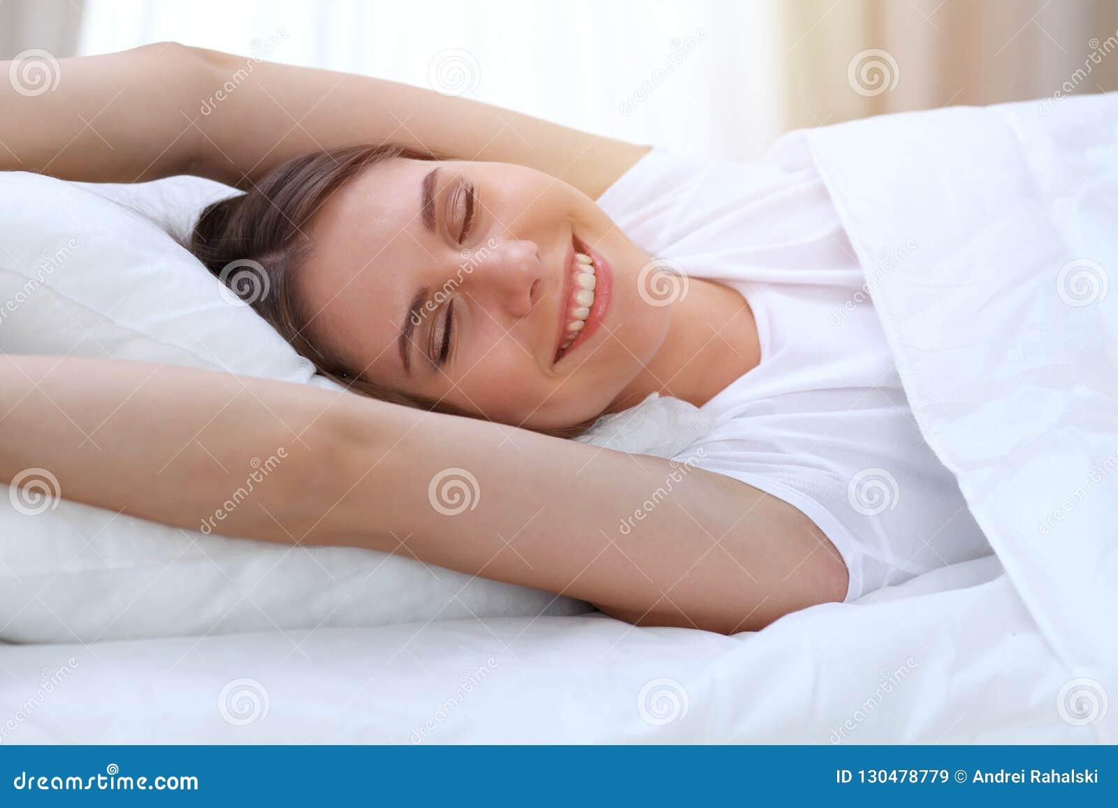 Die schöne junge und glückliche Frau, die Hände ausdehnt, beim im Bett bequem liegen und vor himmlisch lächeln wachen herein auf