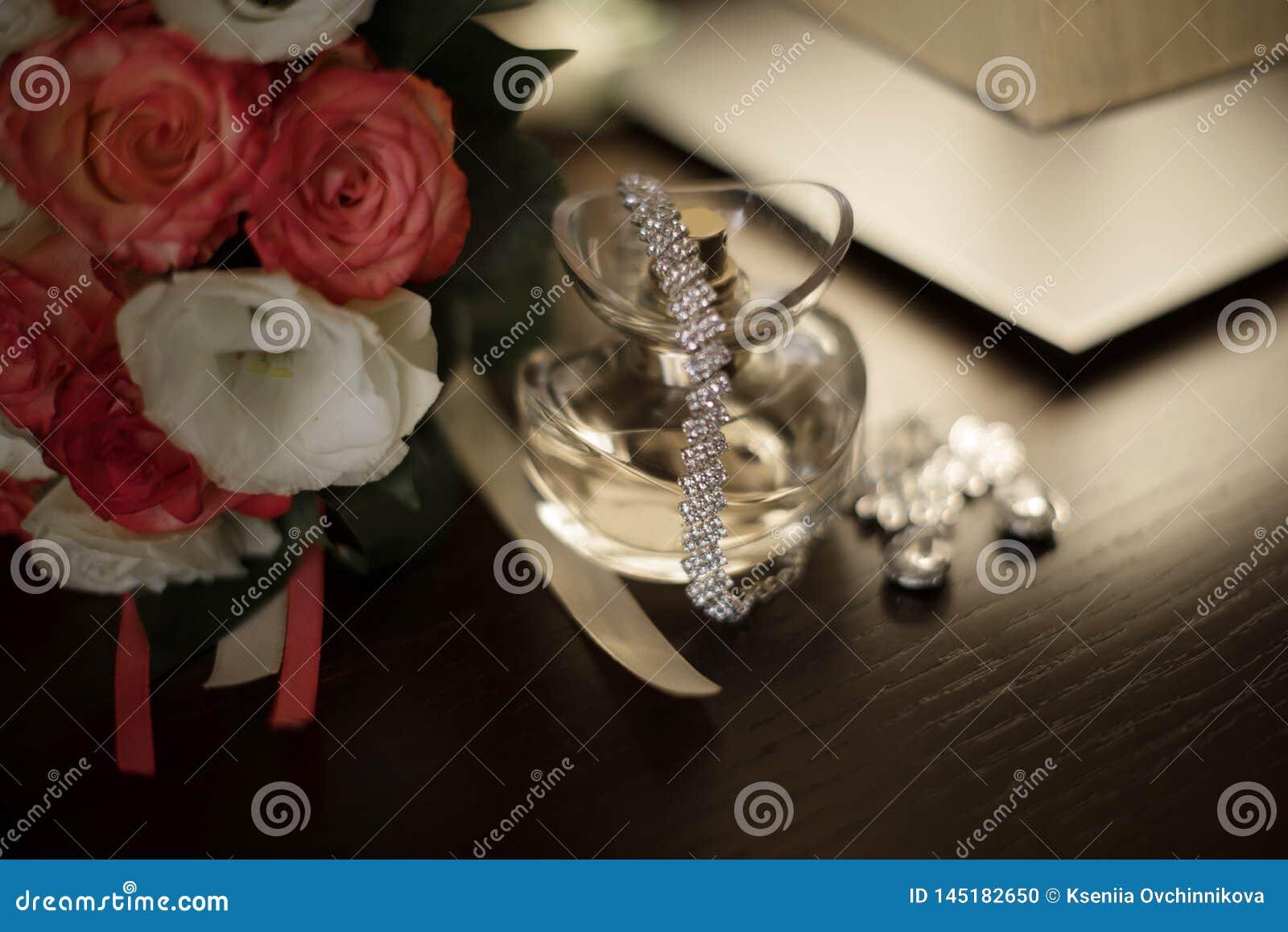 Die Schuhe der Frauen, Parfüme, Einladungskarten, Eheringe auf einem lokalisierten Hintergrund für die Braut