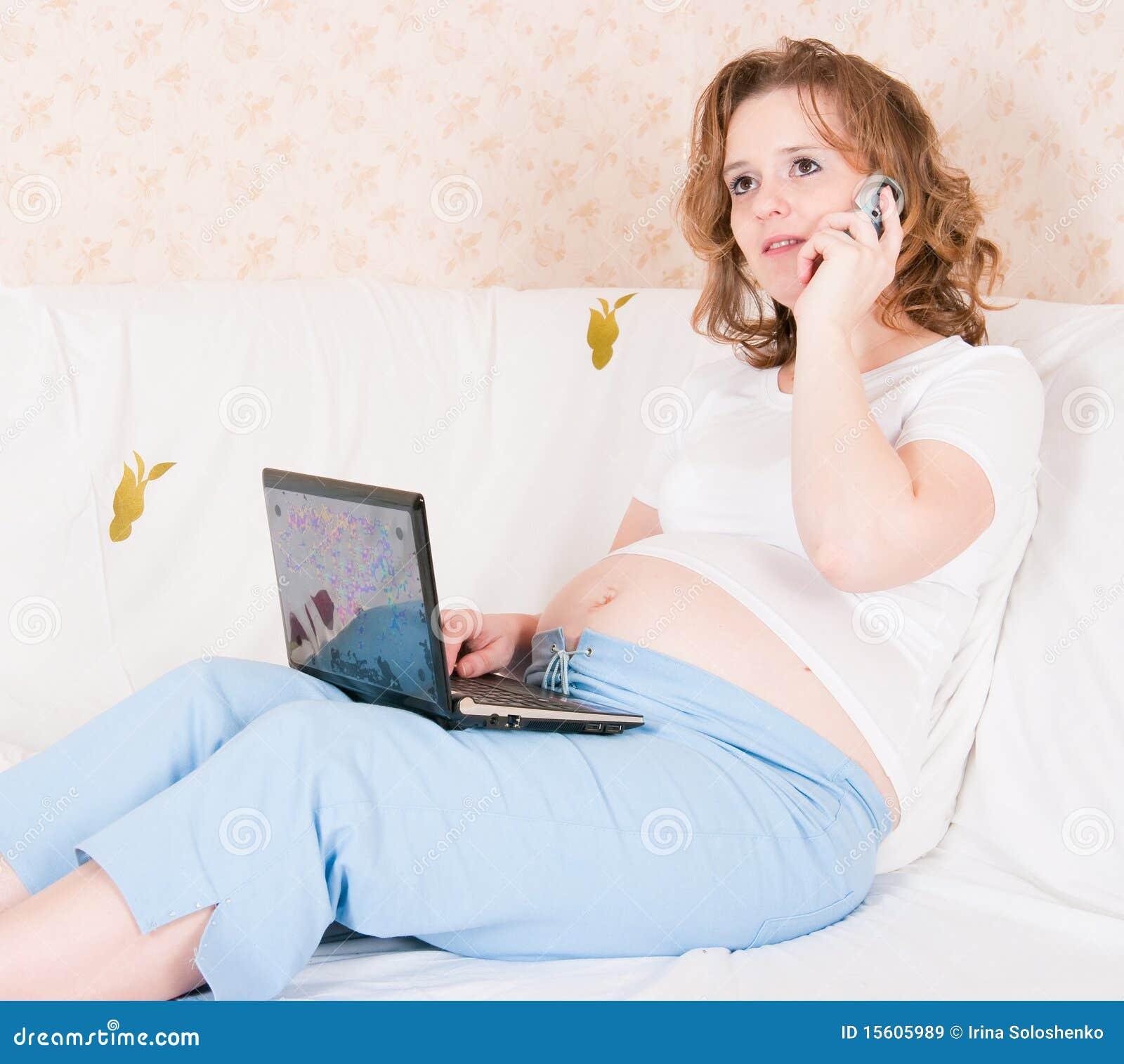Die schwangere Frau mit dem Laptop und dem Telefon