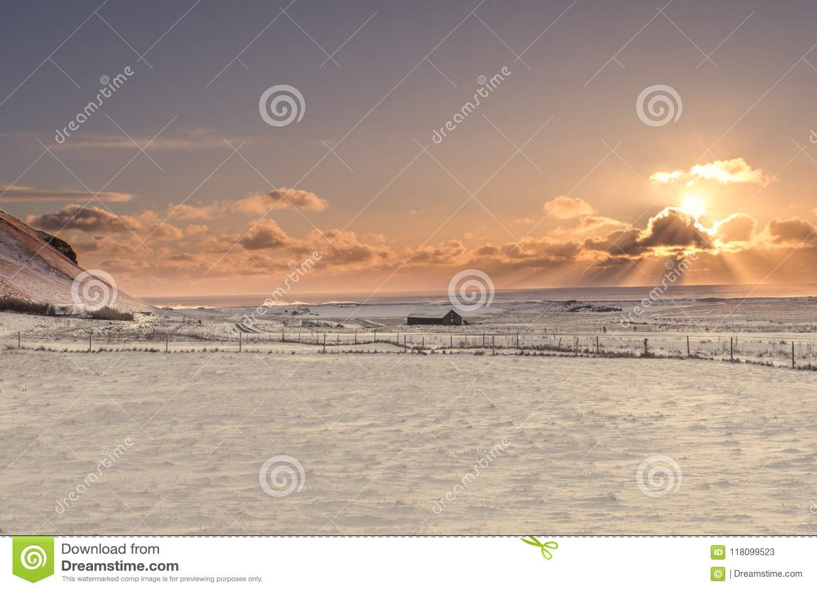 Die Sonne birst von hinten eine Wolke über der gefrorenen Landschaft von