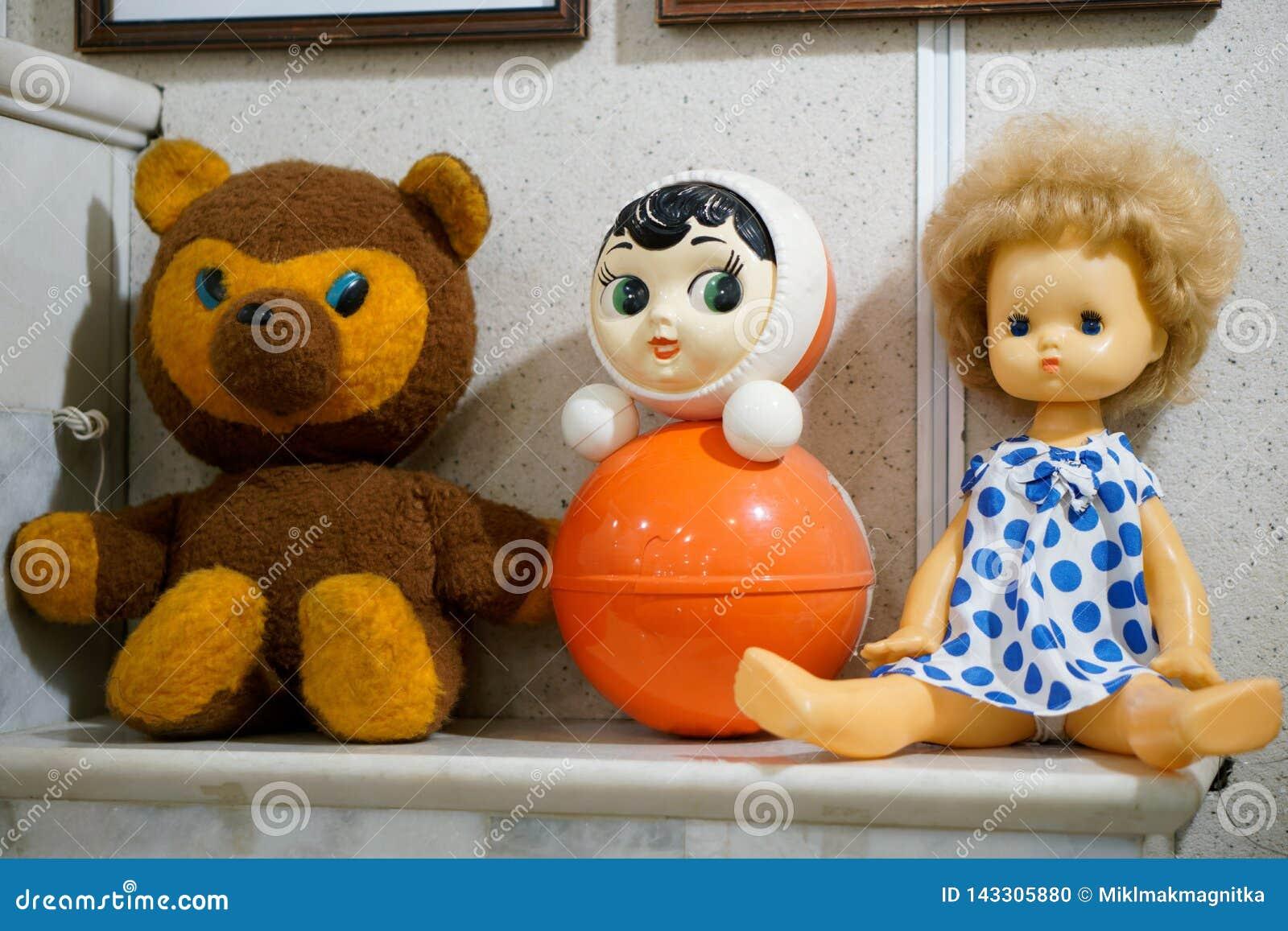 Die Spielwaren der alte Weinlesekinder - eine Puppe, ein Bär und eine Trommel auf einer Kamineinfassung