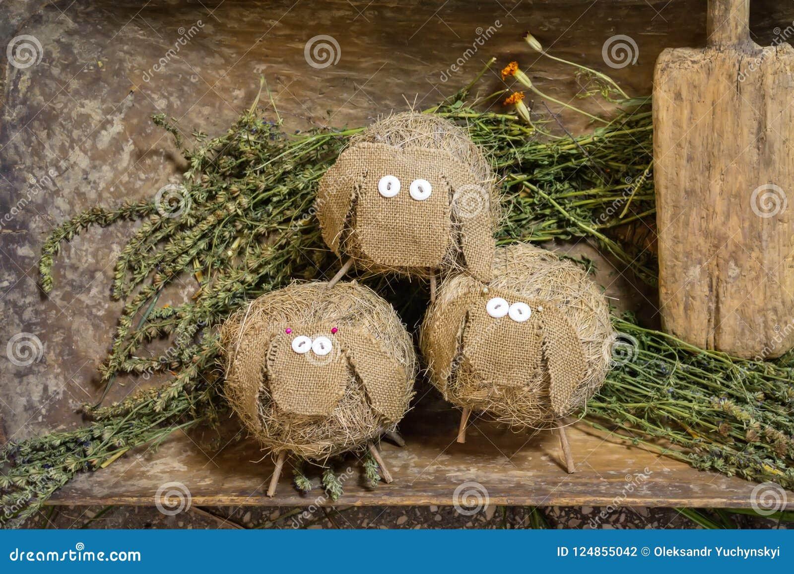 Die Spielzeugschafe, die vom Stroh und vom Stoff gemacht werden, stehen auf gemähtem Gras