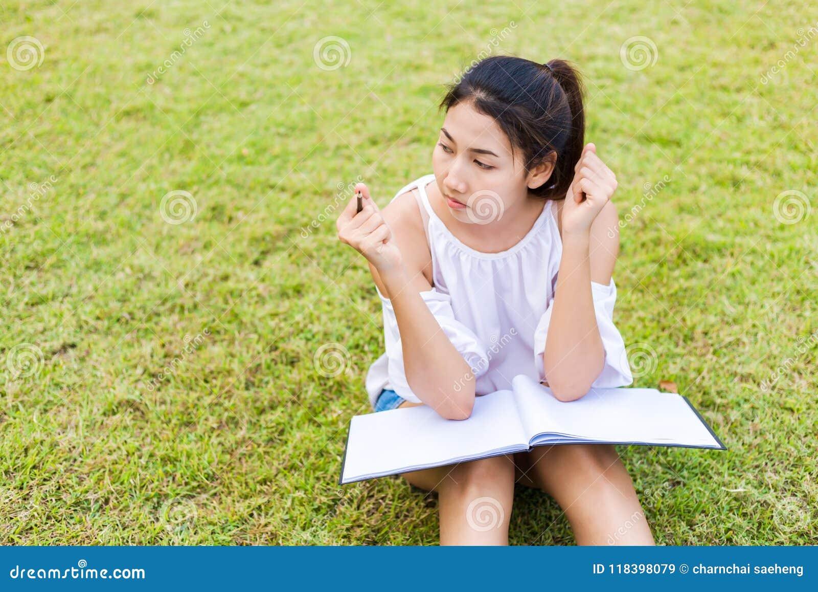 Die Studentin, die auf dem Gras und dem Weißbuch auf Knie sitzt Ihre Hand, die Bleistift hält
