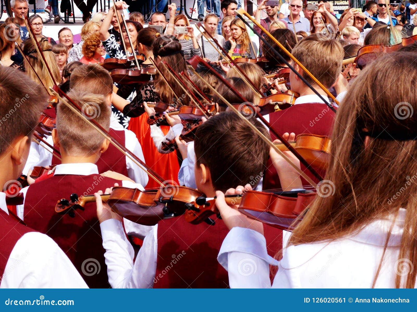 Die Violine an einer Karnevalsprozession zu Ehren des Feierns des Stadt ` s Tages spielen
