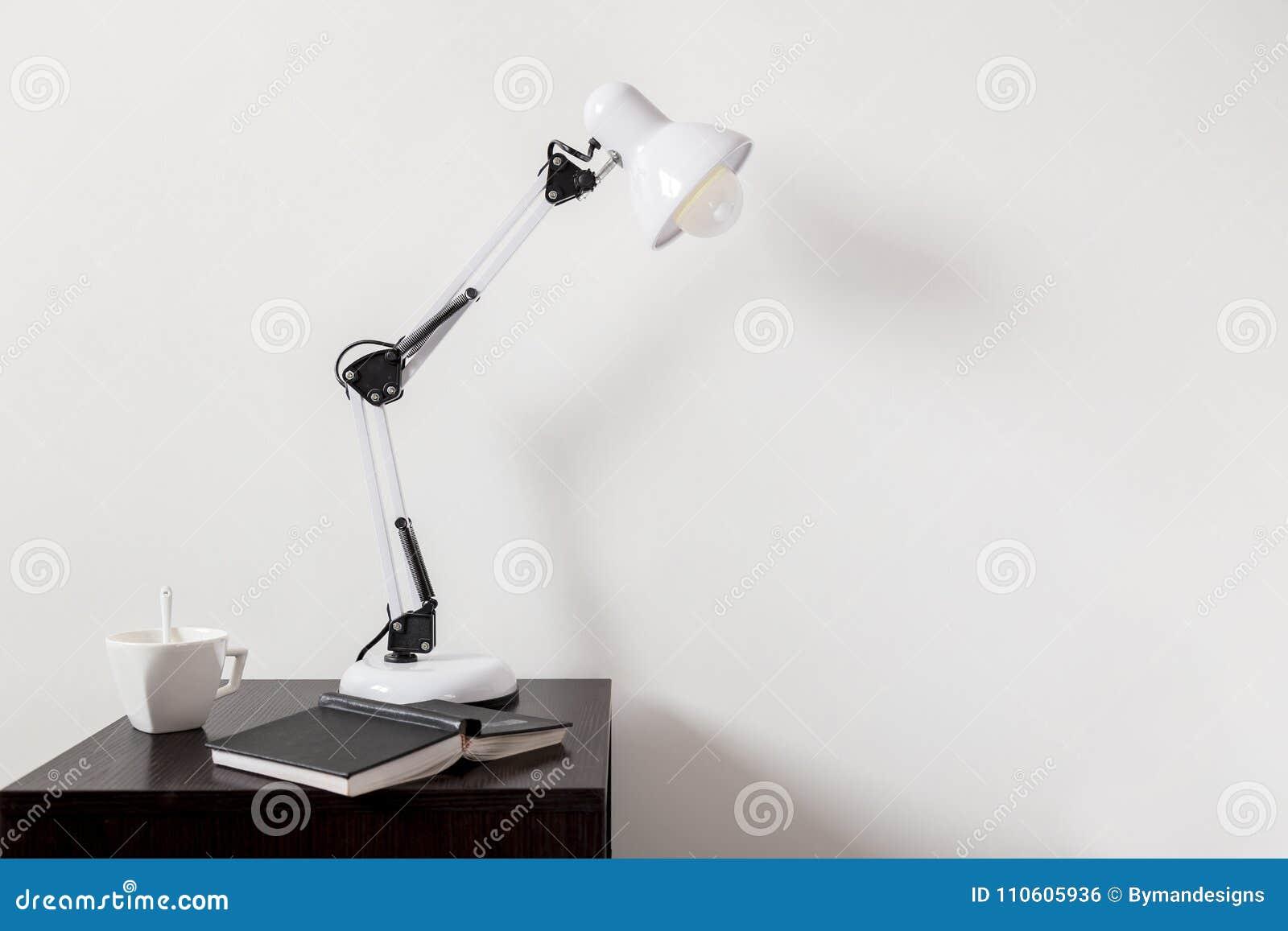 Die weiße Lampe auf dem Kopfende nahe bei einem Buch und einer Tasse Tee