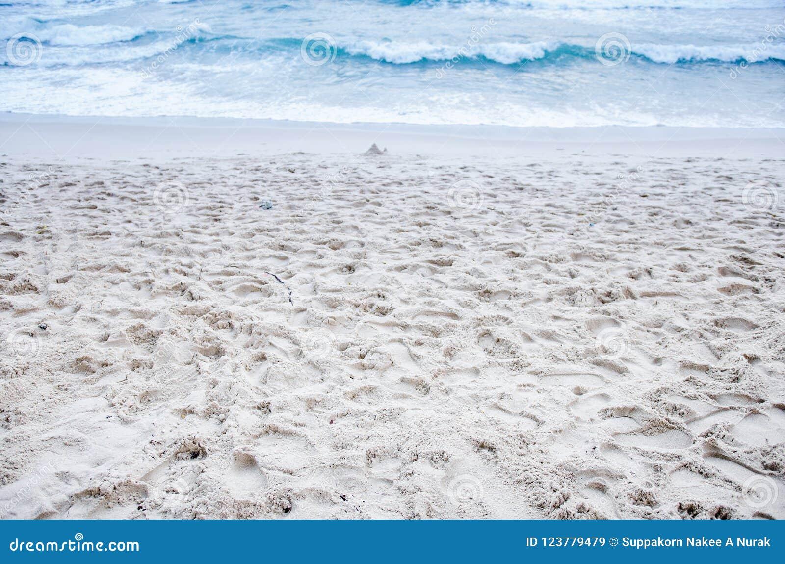 Die Wellen peitschen weißen Sand