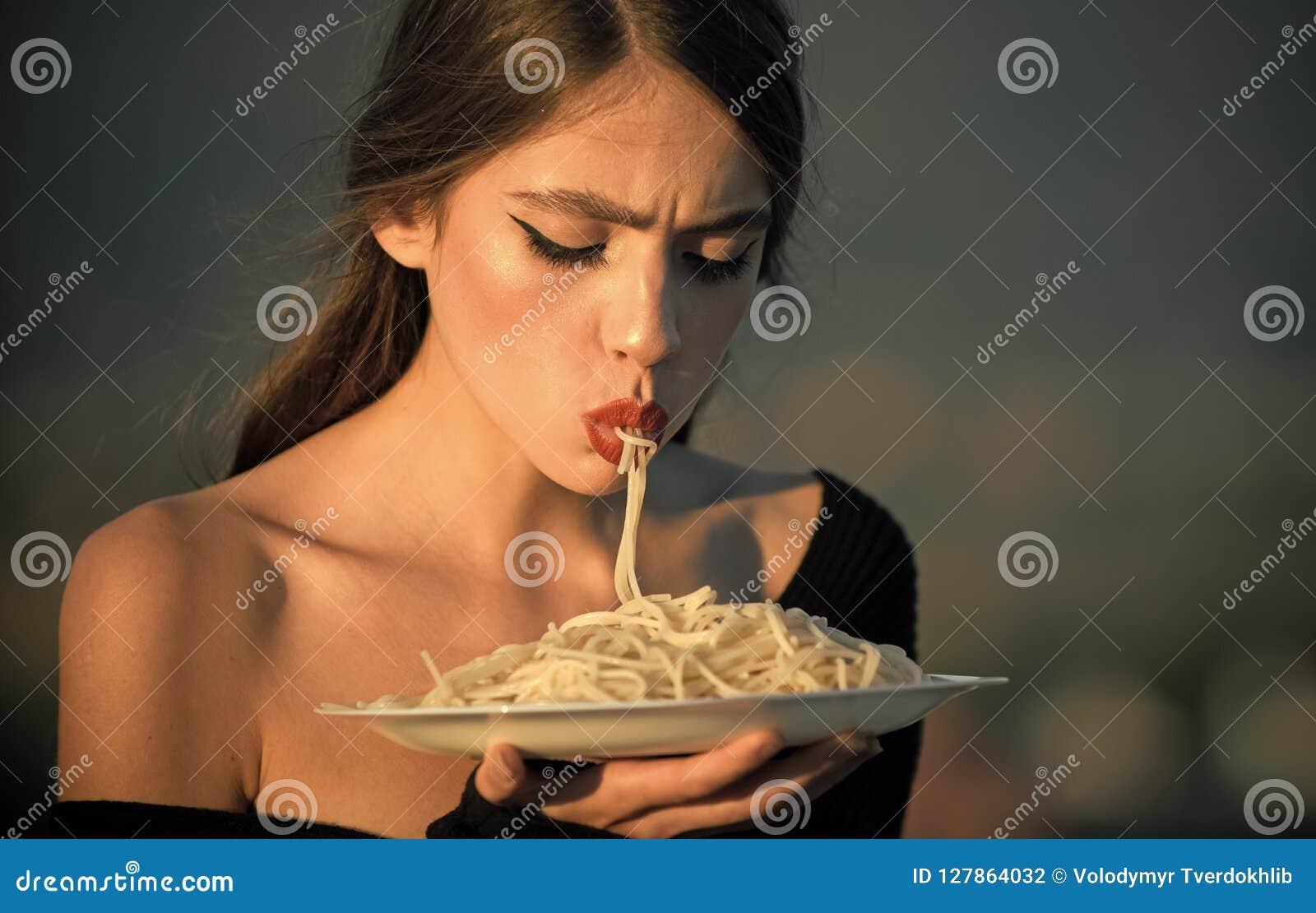 Dieet en gezonde natuurvoeding, Italië De chef-kokvrouw met rode lippen eet deegwaren Honger, eetlust, recept Vrouw die Deegwaren