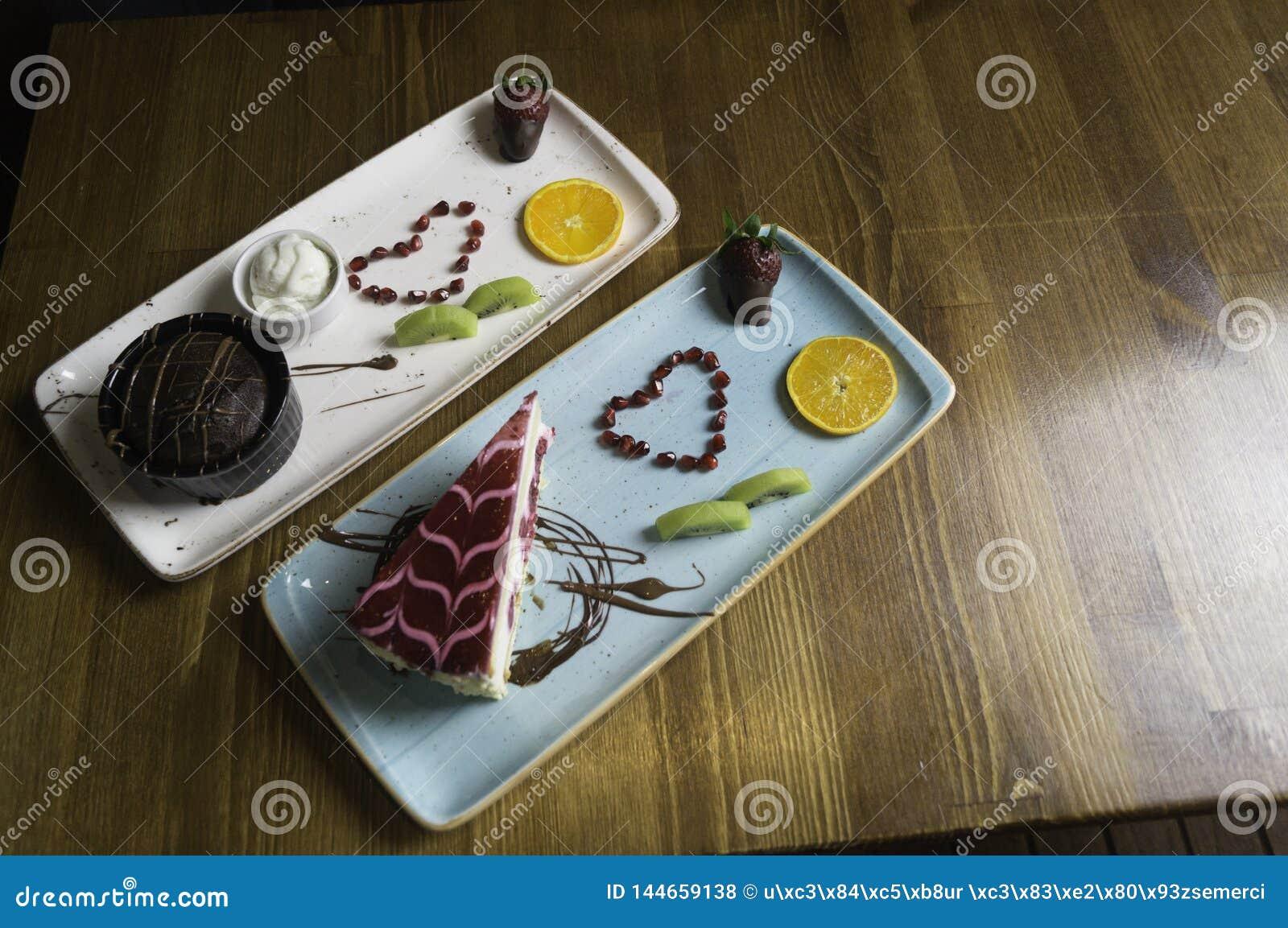 Dienbladtribunes op gesneden chocoladecake en sinaasappel