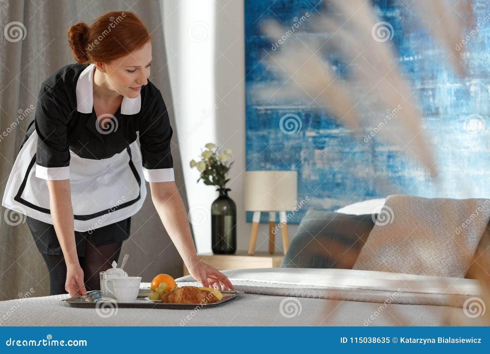 Dienstmeisje die dienblad met voedsel zetten