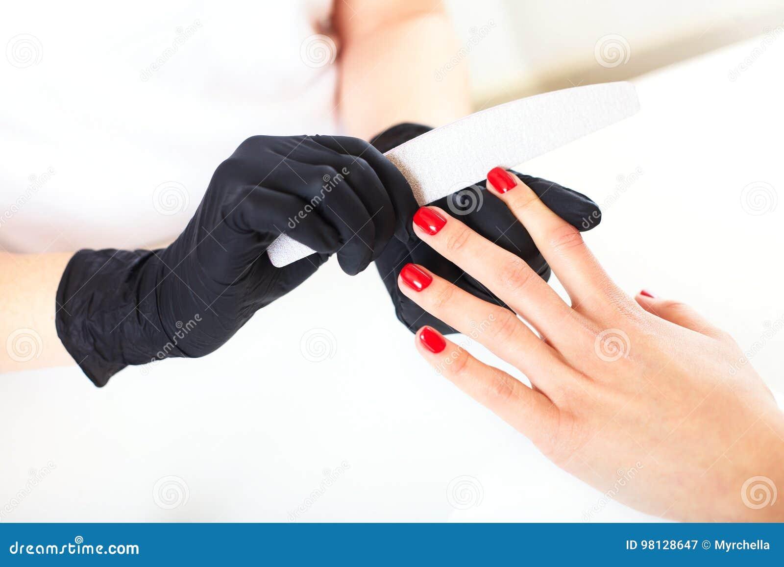 Dient handschoenenzorgen over handenspijkers in De salon van de manicureschoonheid
