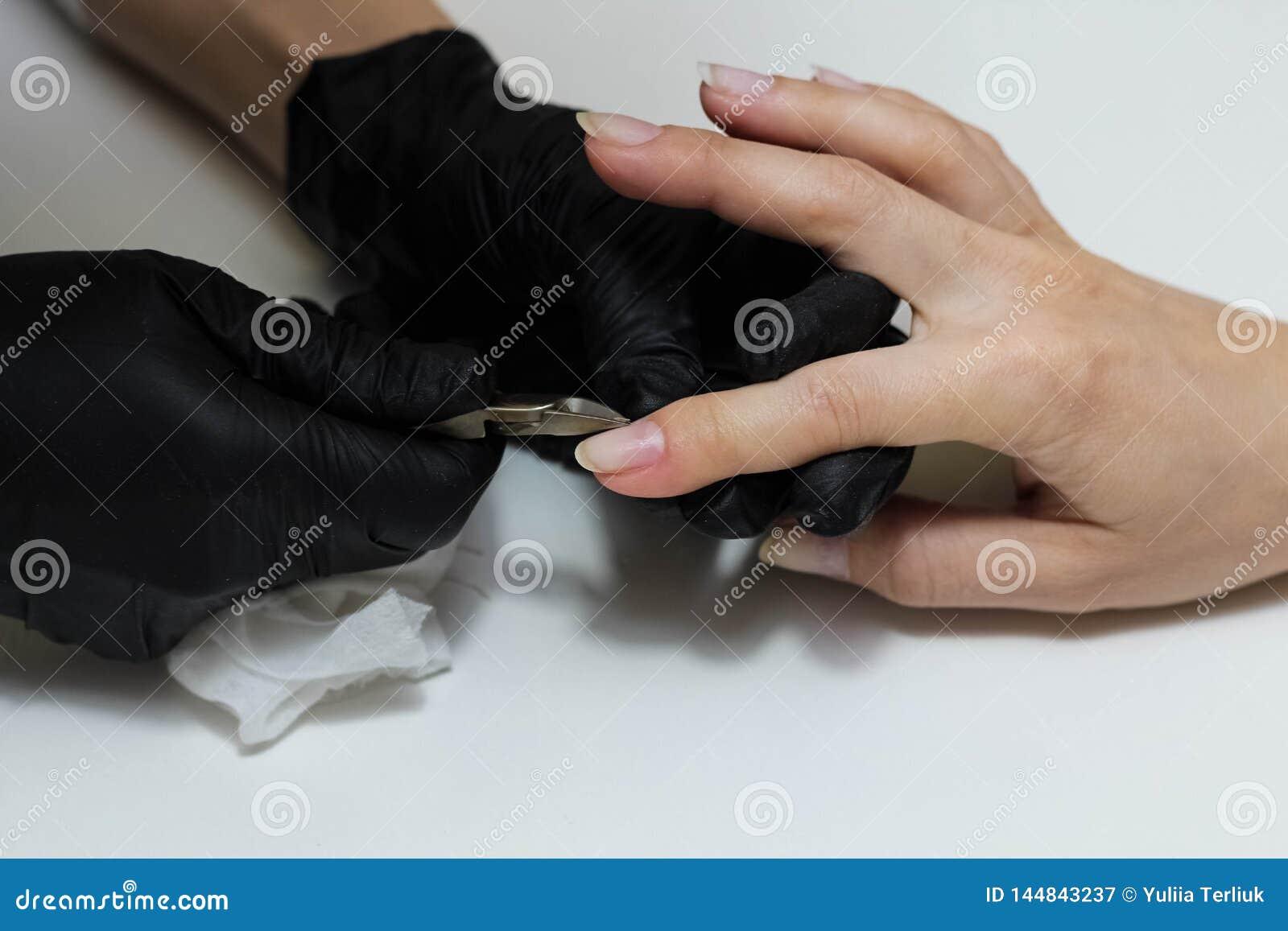 Dient zwarte handschoenenzorgen over handenspijkers in De salon van de manicureschoonheid Spijkers die met dossier indienen